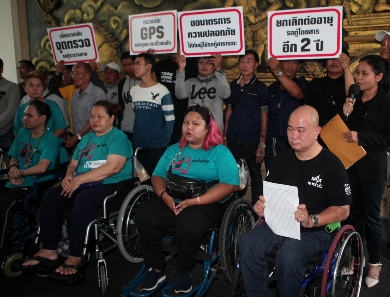 Activists, including wheelchair-bound victims of road accidents, rally at the Transport Ministry to call for tighter safety standards on public transport and demand the replacement of old public vans be made compulsory.Apichart Jinakul