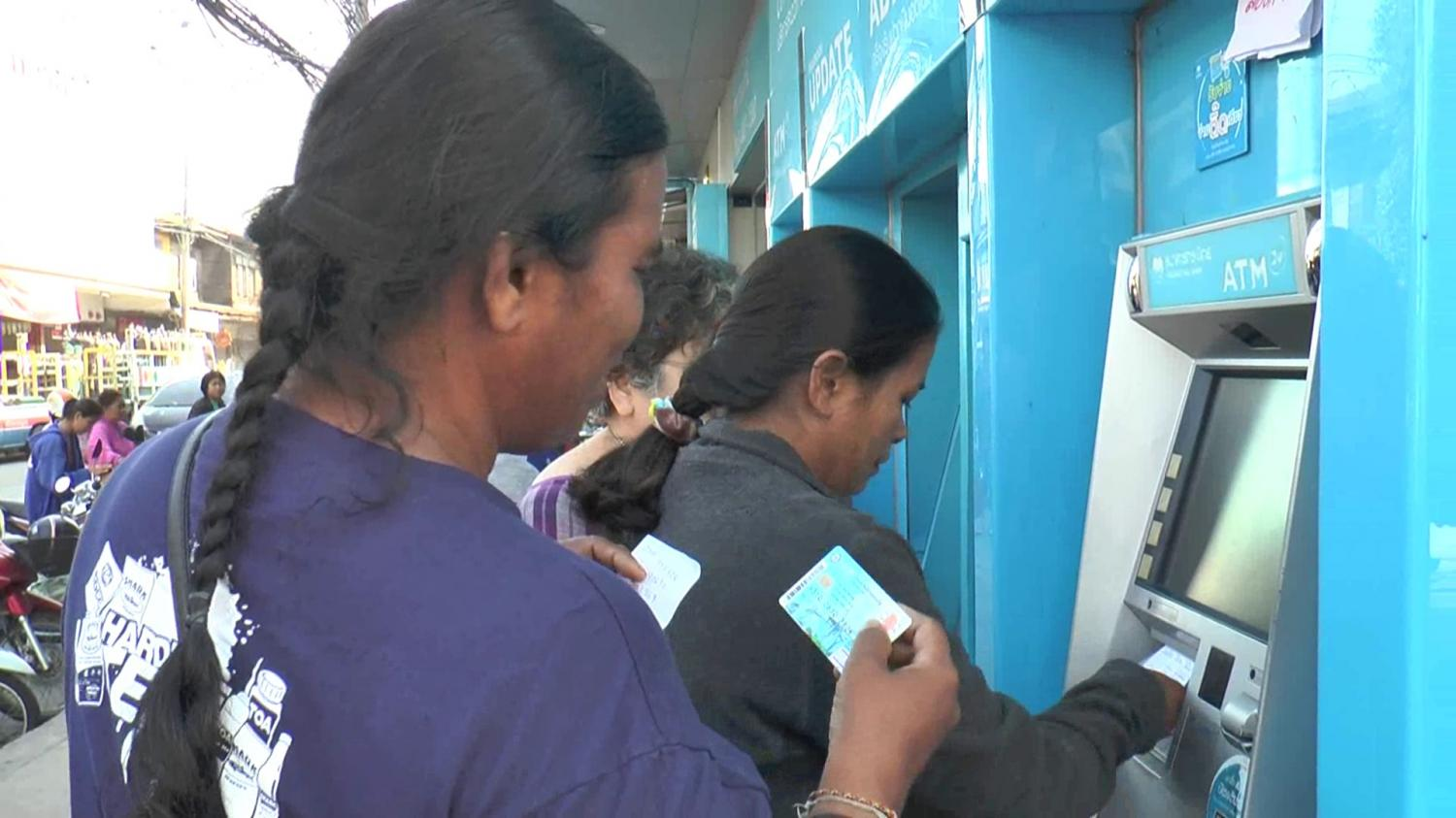 Welfare cardholders queue up at a Krungthai Bank ATM to withdraw money provided by the government. SURACHAI PIRAKSA
