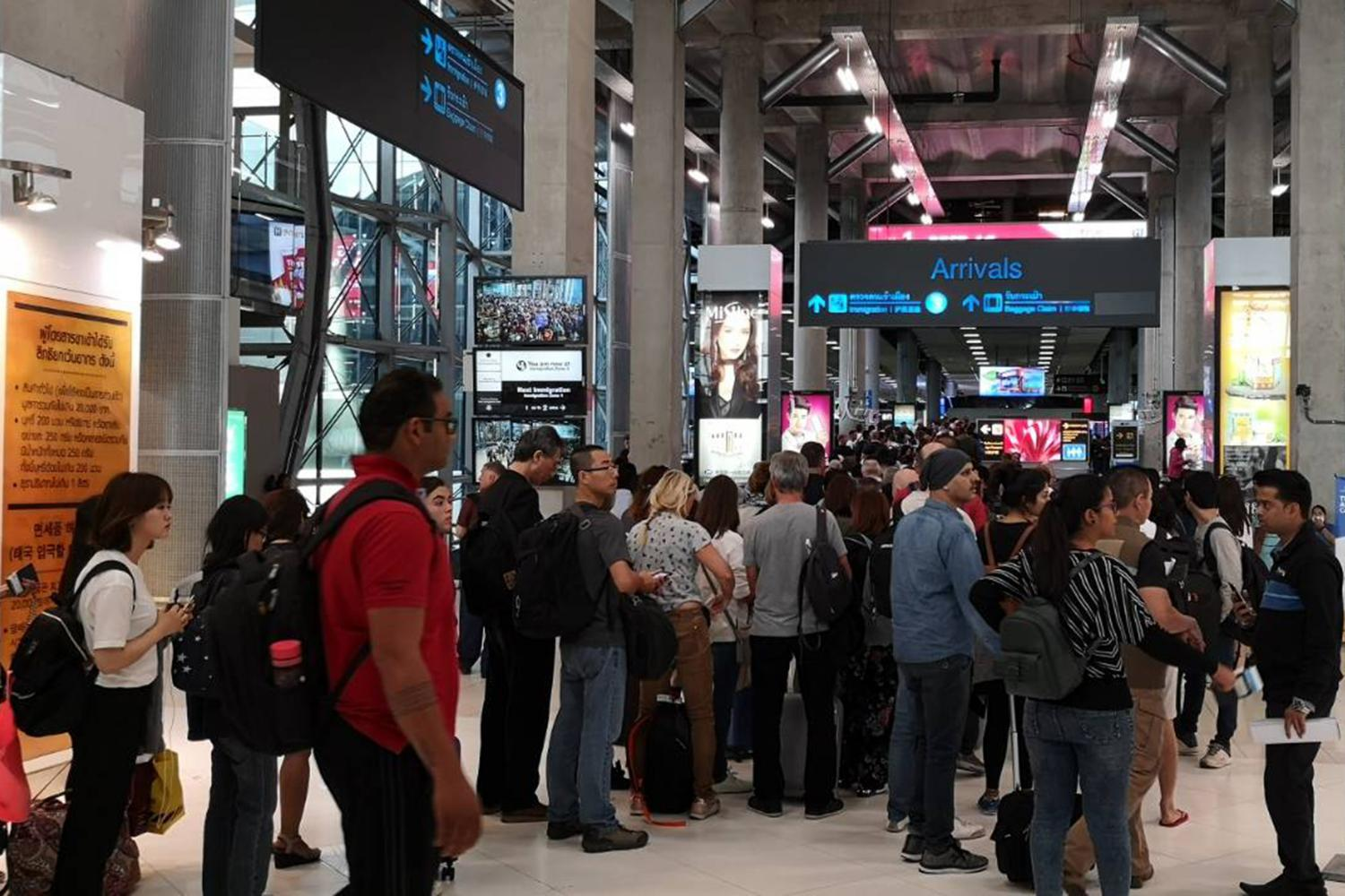 Tourists queue up in lengthy lines for immigration checks at Suvarnabhumi airport. (Bangkok Post photo)