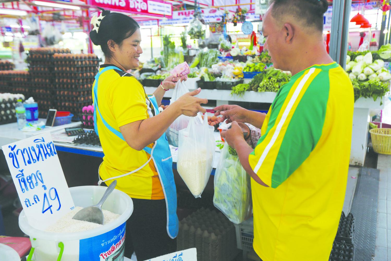 A man buys a pack of rice at a market in Bangkok. The government has launched a new financial package to boost the economy. VARUTH HIRUNYATHEB