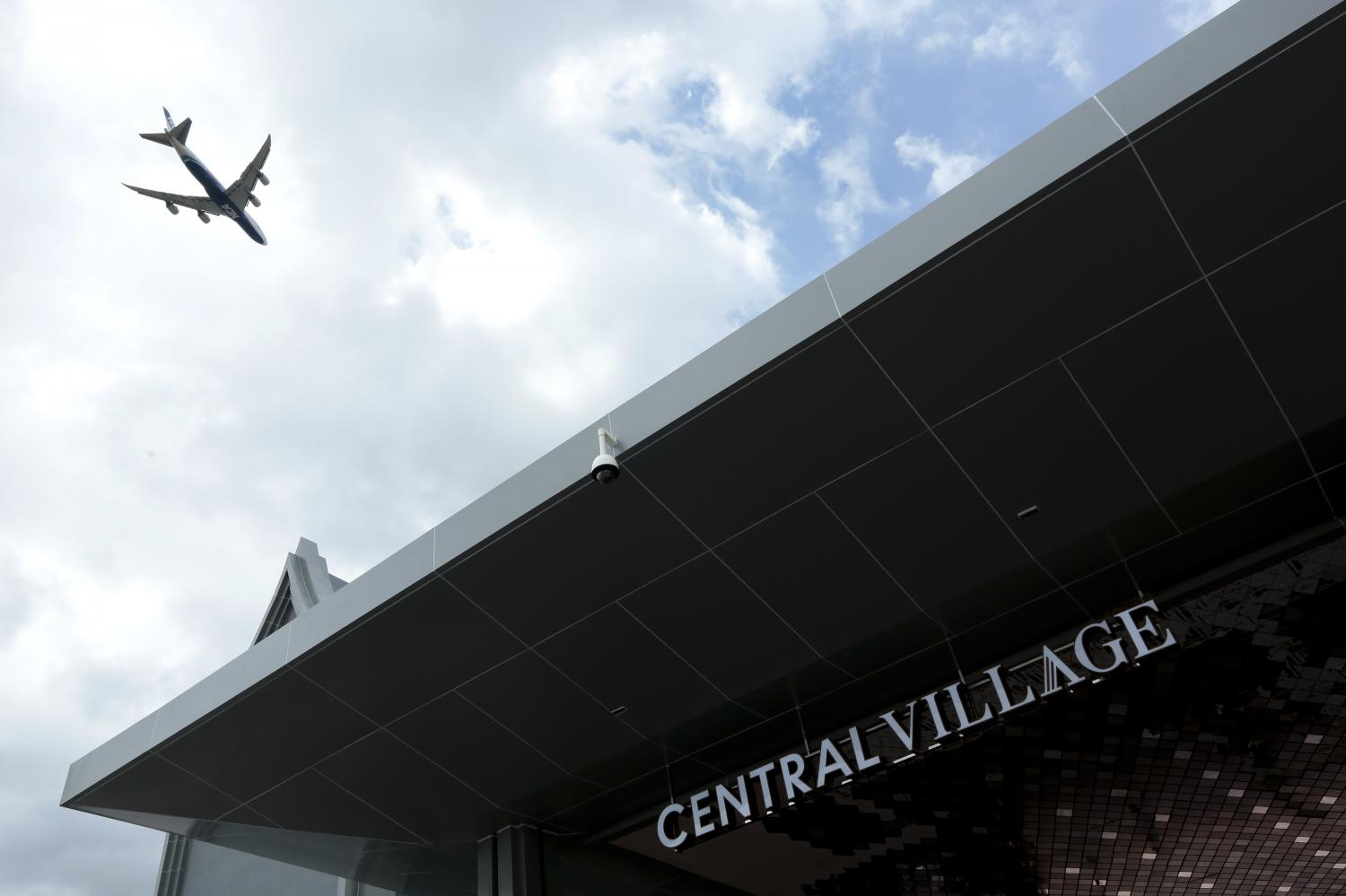 A plane flies over Central Village, a luxury outlet near Suvarnabhumi airport. (Photo by Patipat Janthong)