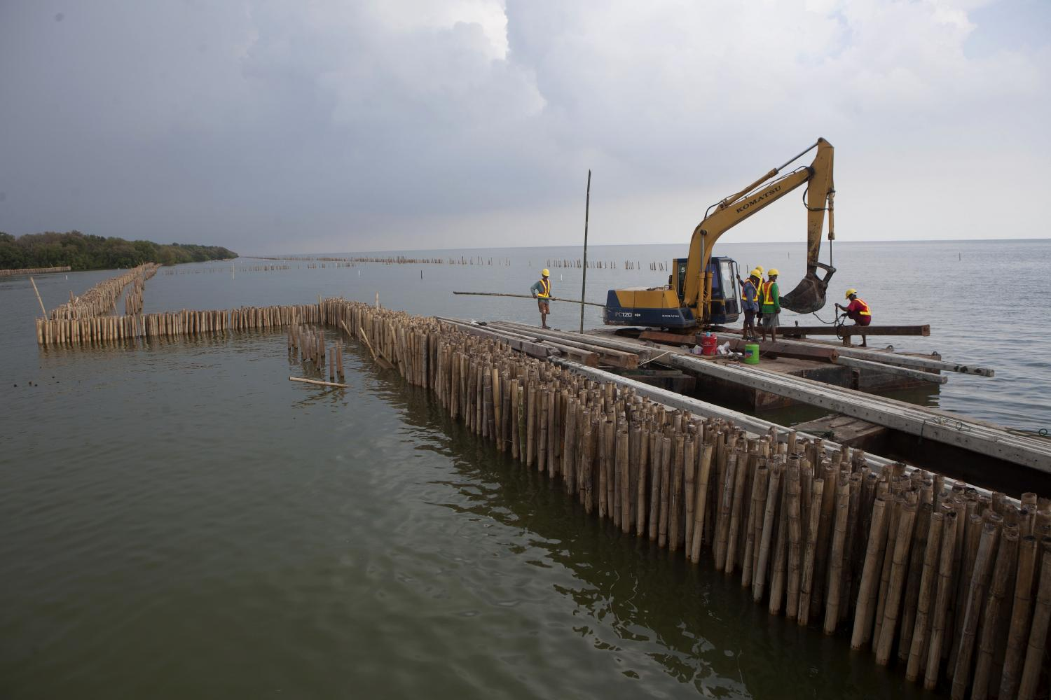 Heavy machinery is deployed to sink concrete poles along the shoreline off Bang Khunthian district of Bangkok to prevent coastal erosion. About 400 electricity poles were taken from areas in Bangkok where power lines had been laid underground. They were placed vertically to form a buffer zone against the waves. (Photo by Pawat Laopaisarntaksin)