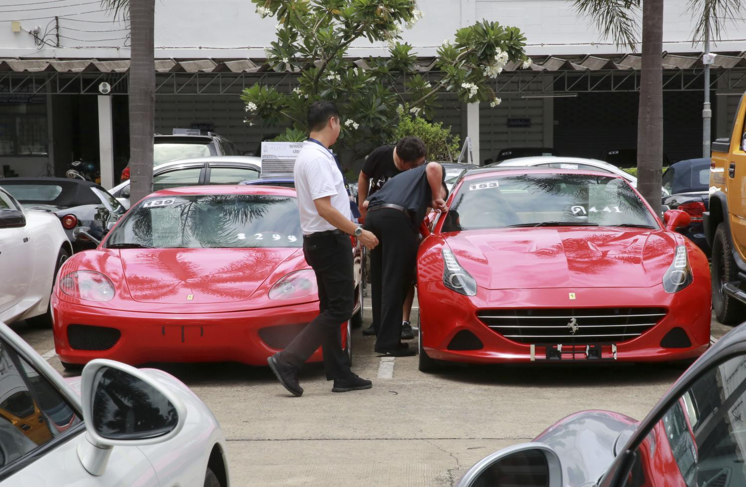 Visitors inspect a Ferrari put up for auction by the Customs Department before the Land Transport Department began refusing registrations in 2017. (Photo by Taweechai Tawatpakorn)