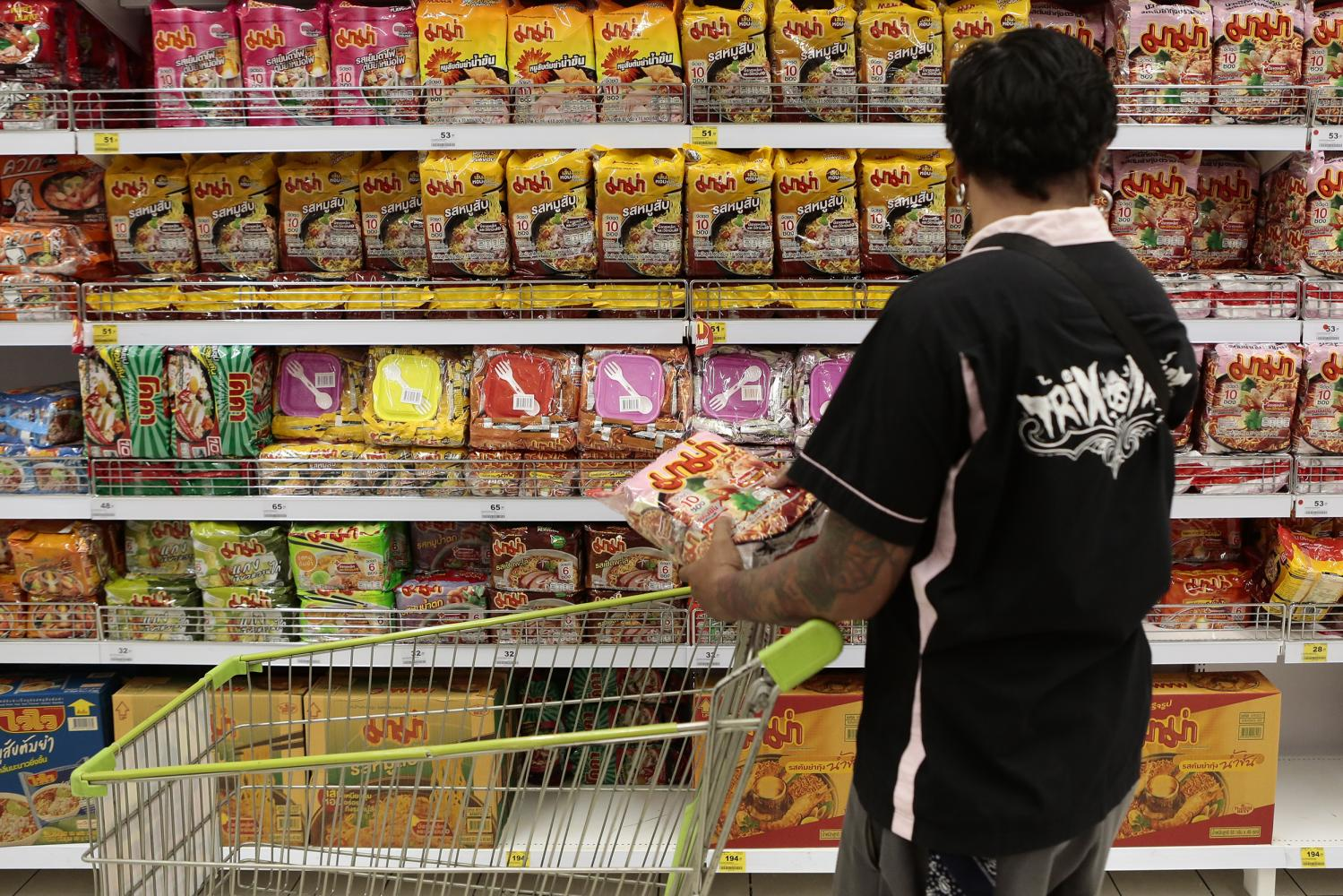 A shopper faces an overwhelming selection of instant noodles at a Bangkok supermarket. Instant foods and snacks with over 2,000mg of sodium will be subject to the salt tax. (Photo by  Patipat Janthong)