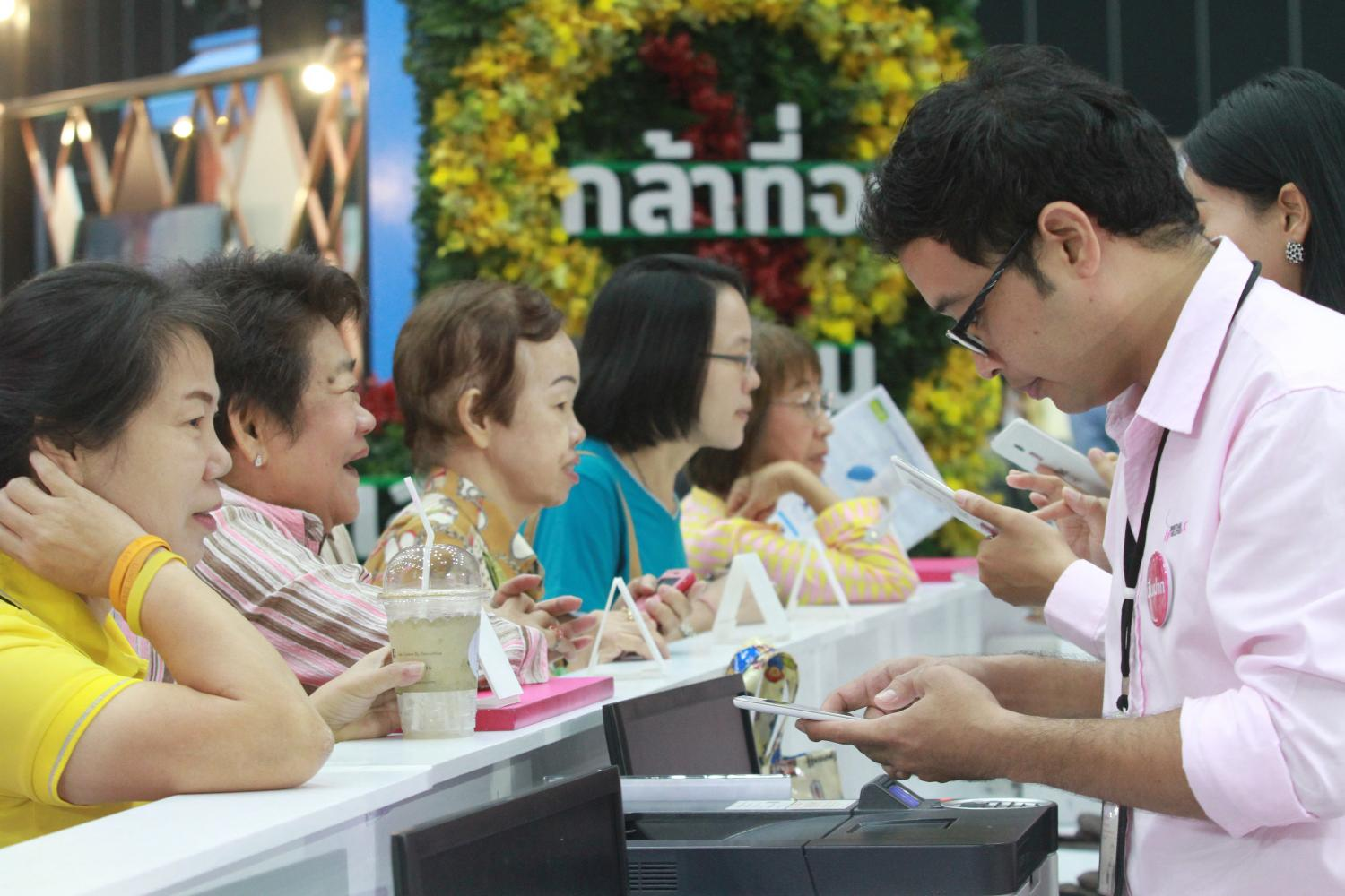 Consumers inquire about loans and other financial services at a money expo in November last year. The high level of household debt has forced the central bank to curb consumer lending.(Photo by Somchai Poomlard)