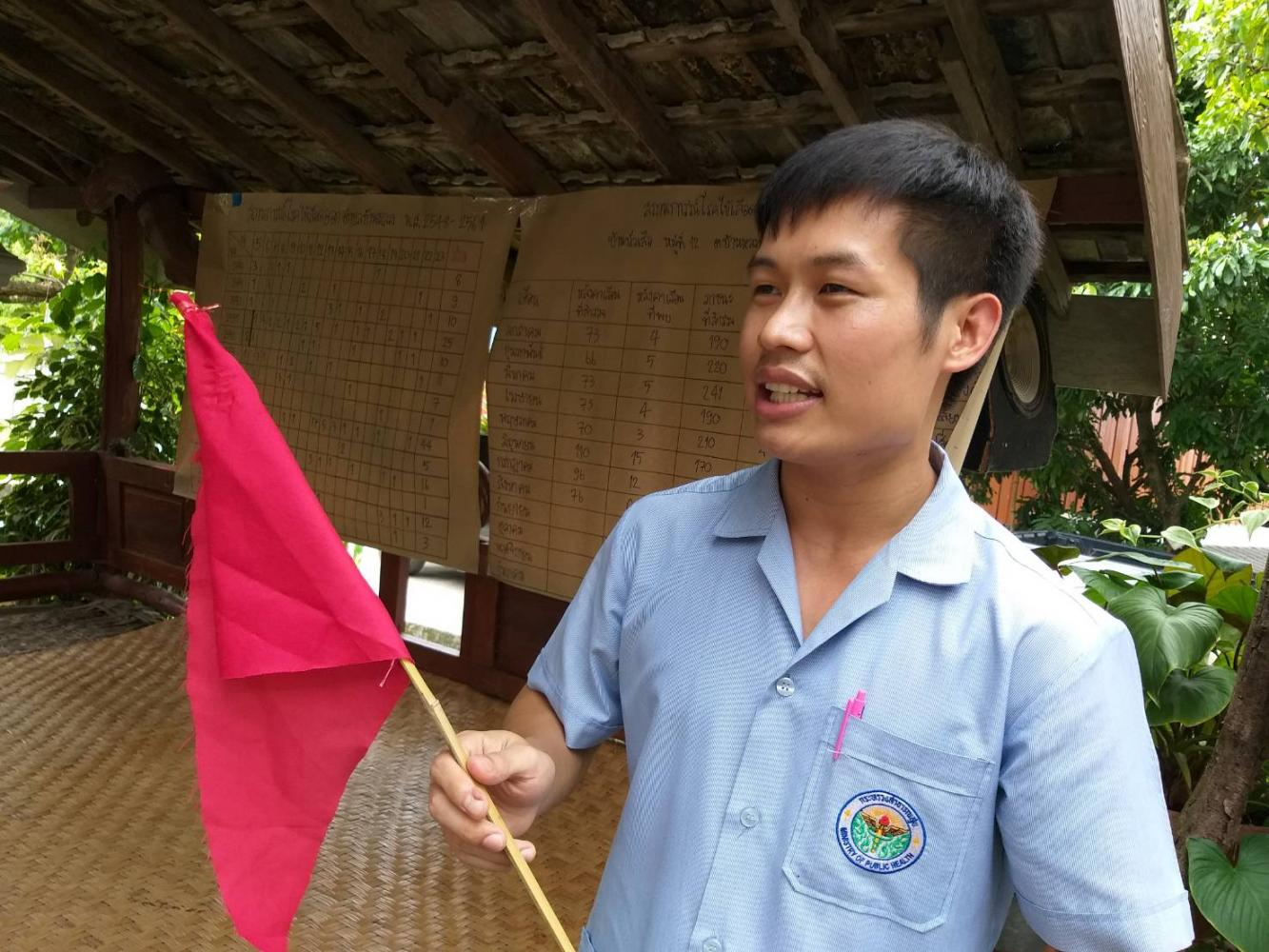 Ekkasit Wongtharahas, a health promotion employee, shows a red flag used to fight the spread of dengue fever in tambon Ban Luang of Chiang Mai. (Photo by Onnucha Hutasingh)