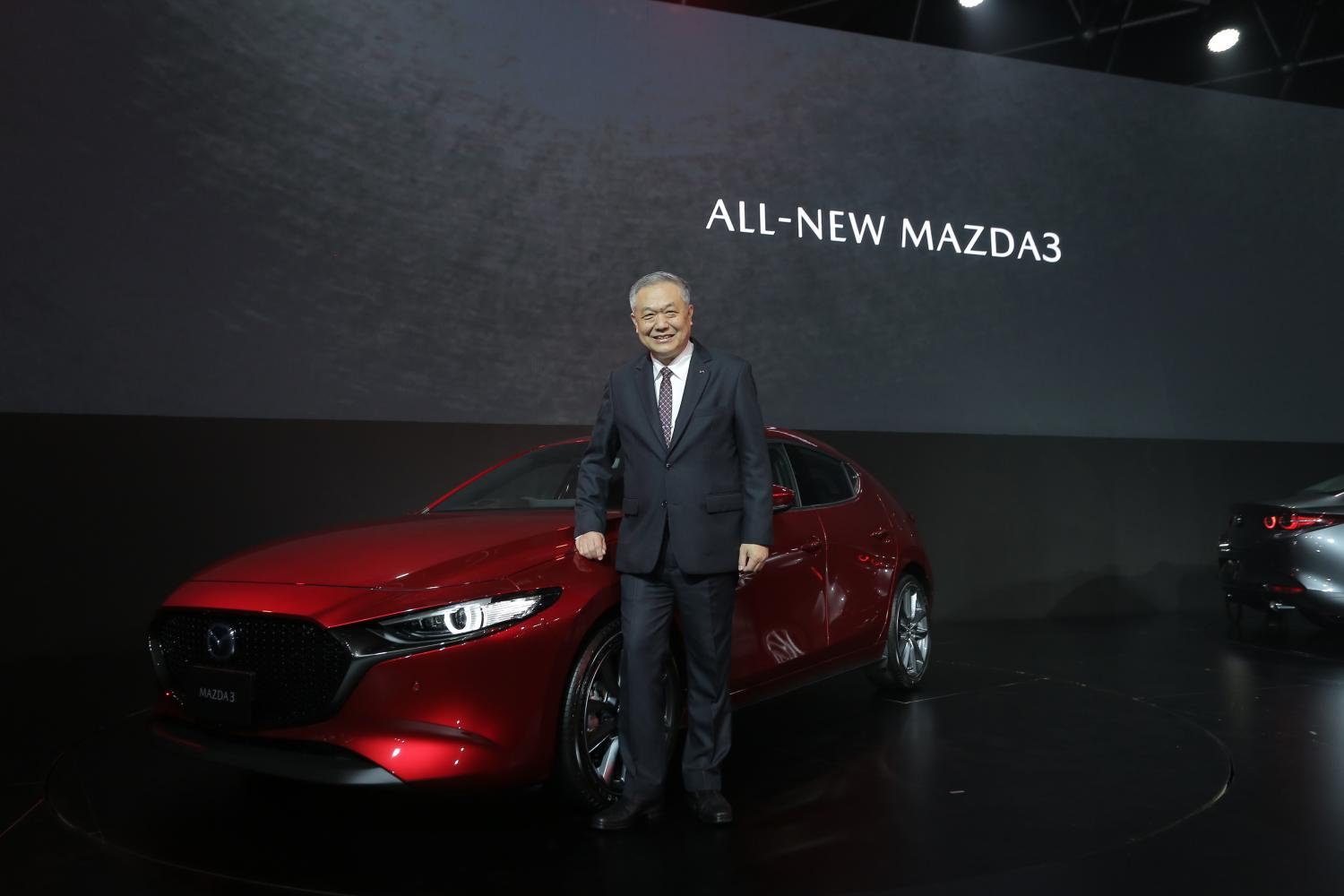 Chanchai Trakarnudomsuk, president of Mazda Sales Thailand is standing with all-new Mazda 3, expecting to sell 7,000 cars for Mazda 3 annually amid a bearish sentiment of local car market.