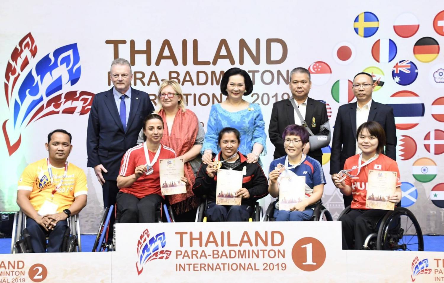 Wheelchair champion Amnouy Wetwithan (centre front) is congratulated by Thai badminton chief Patama Leeswadtrakul, standing behind her.