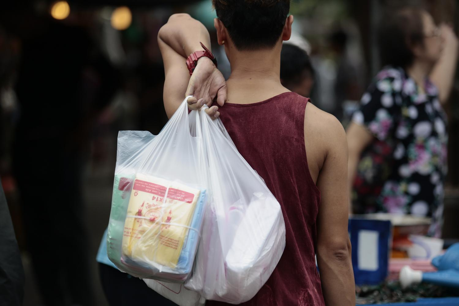 A man carries plastic bags at a market in Bangkok. Thailand is among the world's biggest contributors of ocean plastic waste. PATIPAT JANTHONG