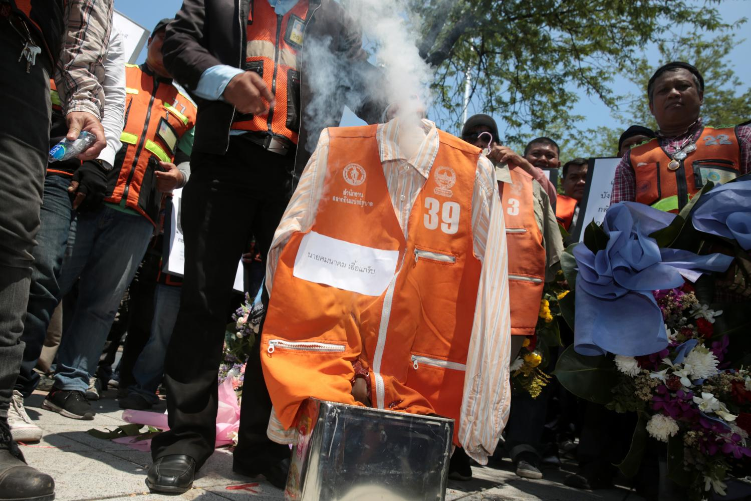 Taxi motorcyclists set a vest alight yesterday during a protest against app-based ride-hailing services at the Transport Ministry. Registered drivers wear an orange vest with the district name and a registration number. Chanat Katanyu