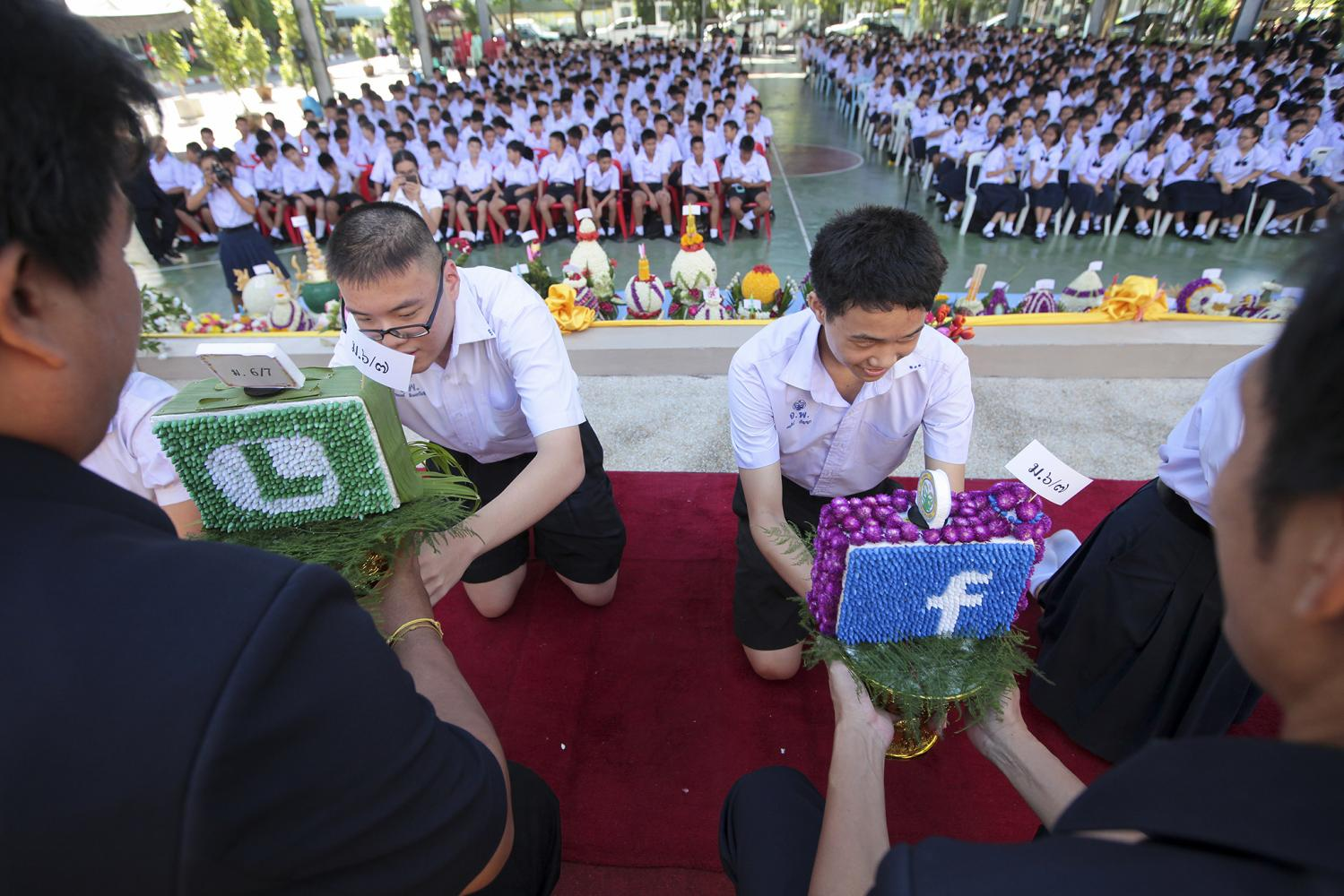 Students at a Bangkok school kneel down and present trays of flowers to their teachers during a 'wai khru' ceremony in June. (Photo by Patipat Janthong)