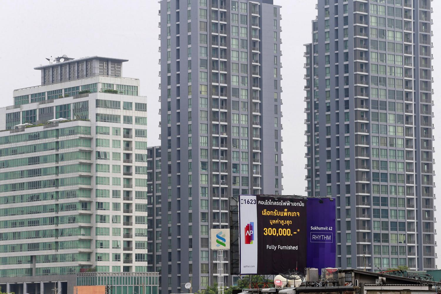 A board advertising discounts on fully furnished condo units is surrounded by high-rise condos in central Bangkok. Officials say the new Bangkok city plan will help condo development flourish.