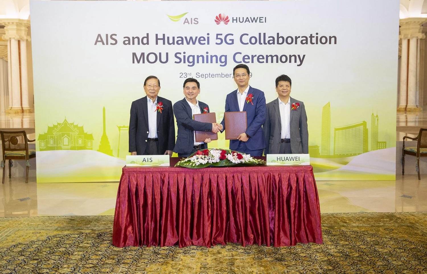 Mr Somchai (second left) and Mr Wu make it official at the signing ceremony for AIS and Huawei's cooperation on 5G technology and services in Thailand.