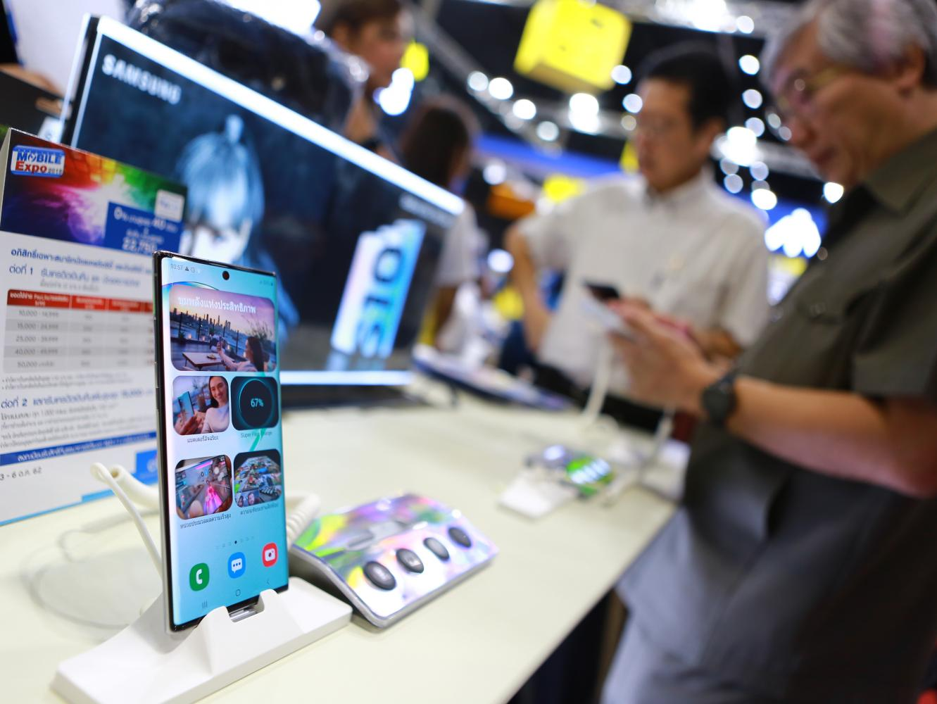 Visitors browse the latest mobile phones on display at Thailand Mobile Expo 2019.(Photo by Somchai Poomlard)