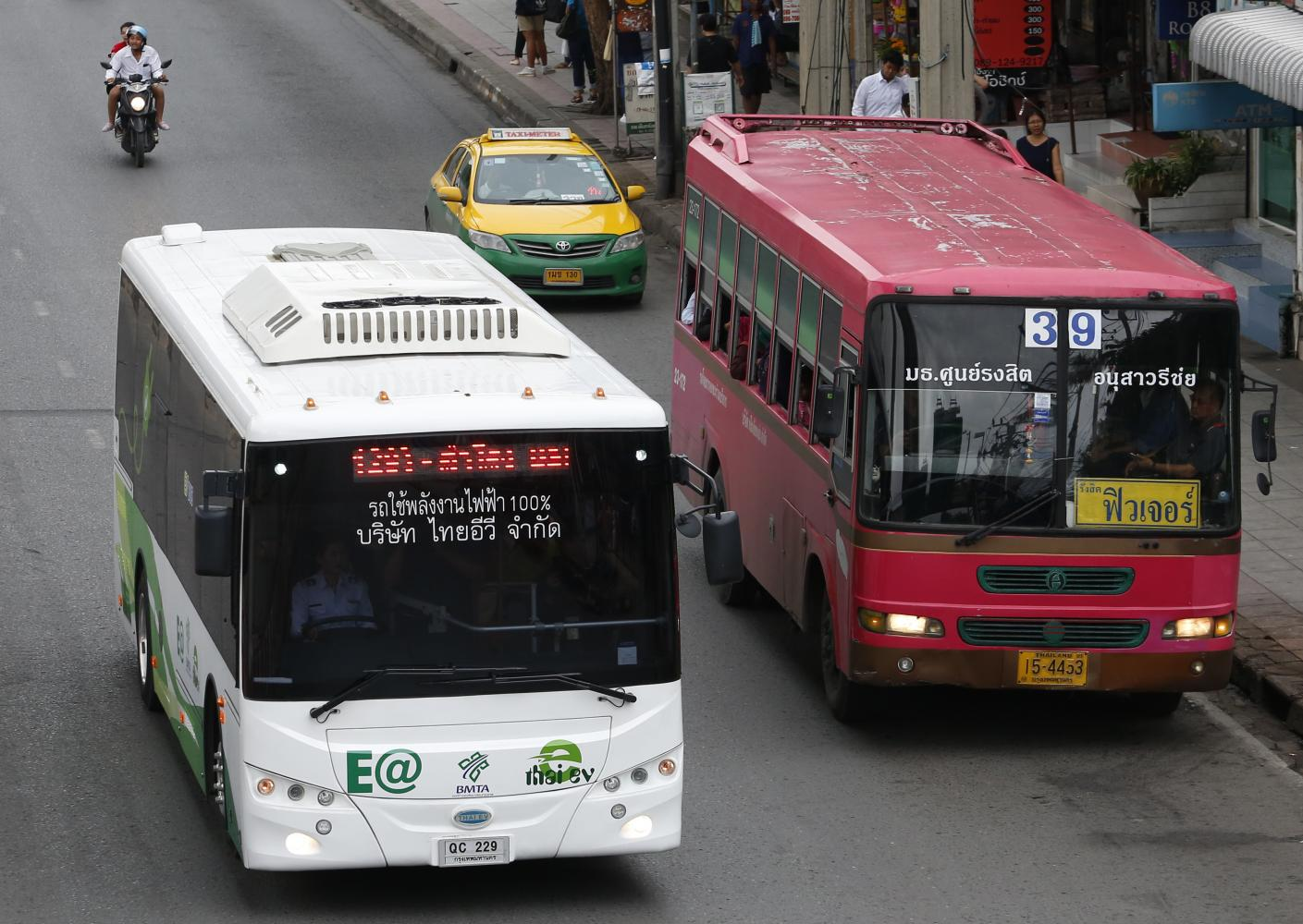 A new electric bus, left, on Phahon Yothin Road in the capital during a test run by the Bangkok Mass Transit Authority. PATTARAPONG CHATPATTARASILL