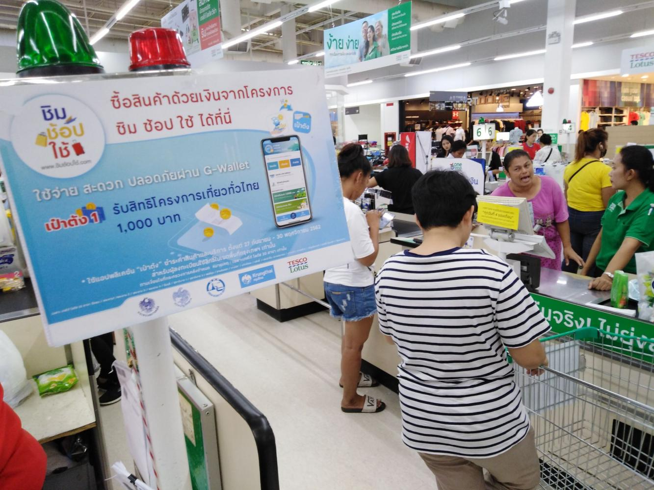 A banner at a Tesco Lotus hypermarket promotes the Taste-Shop-Spend scheme to lure shoppers. The Finance Ministry has blacklisted some operators for inappropriate actions under the scheme.