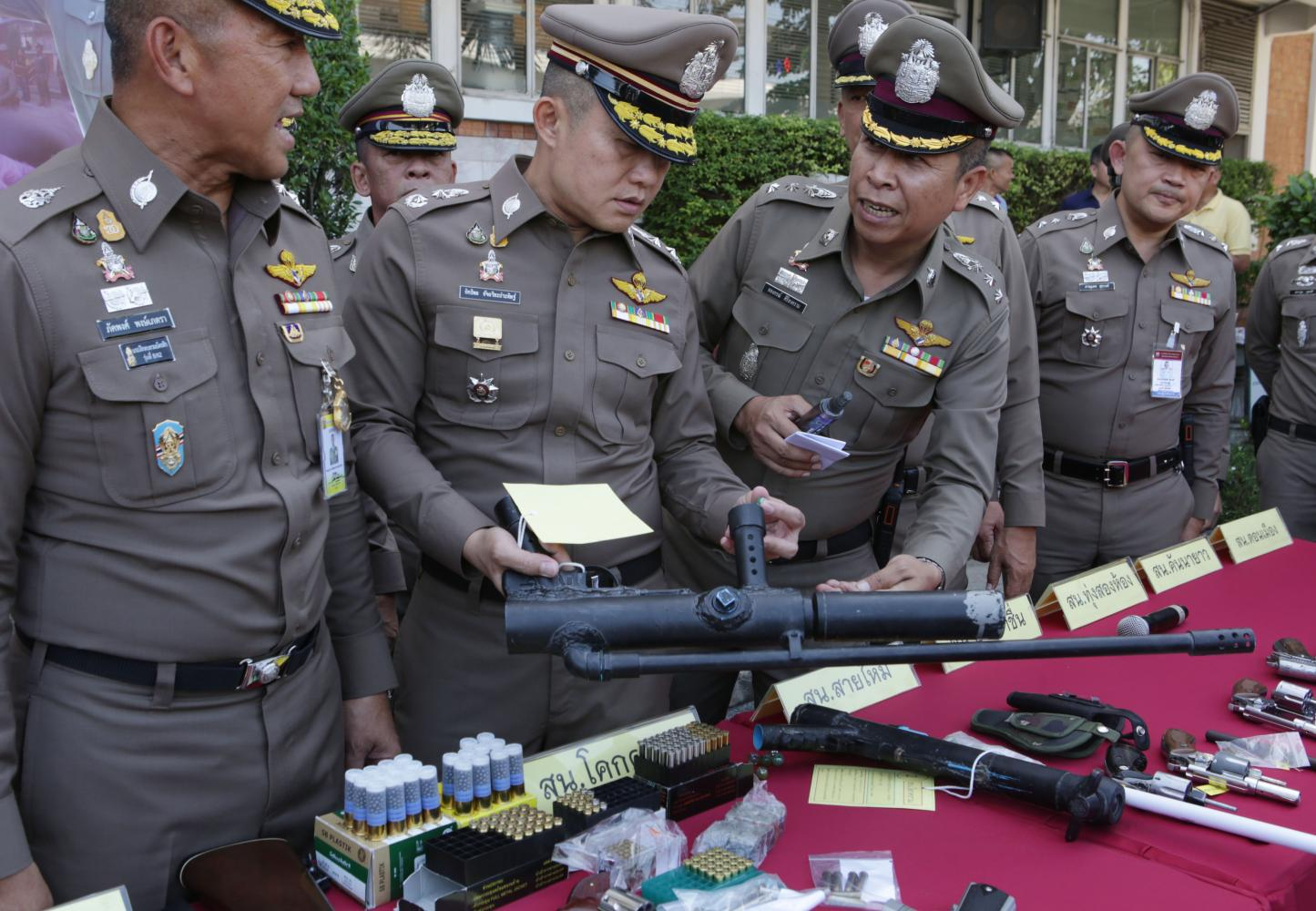 City police chief Pol Lt Gen Phukphong Phongpetra, left, and senior officers inspect one of the 35 illegal weapons seized during a security sweep.(Photo by Apichit Jinakul)