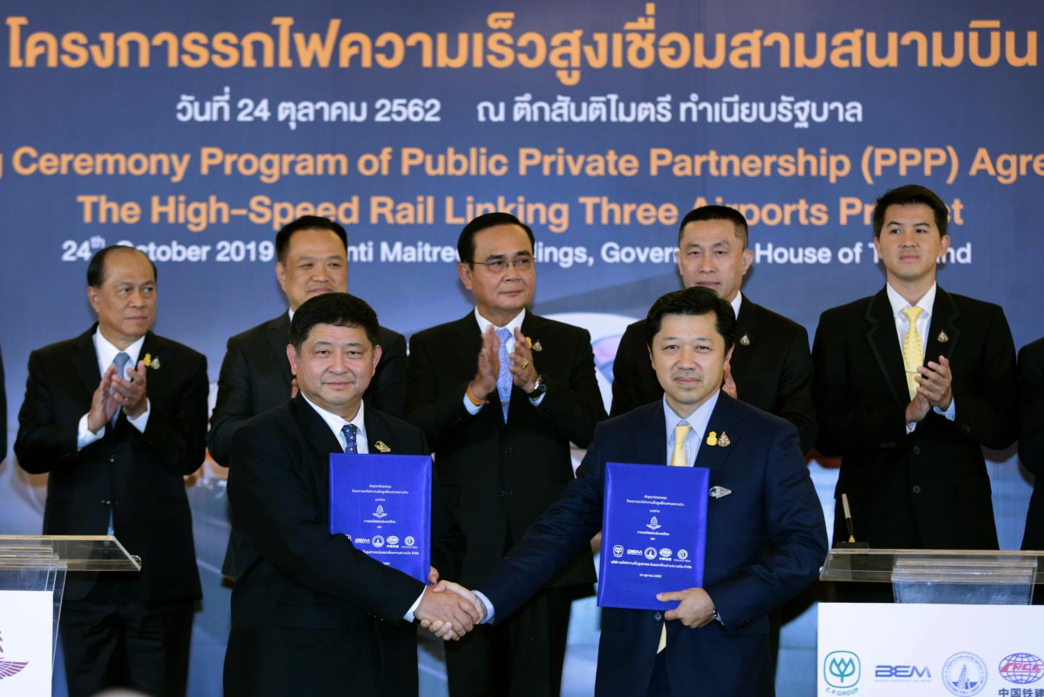 Acting head of the State Railway of Thailand Worawut Mala ( front left) and Charoen Pokphand Group CEO Suphachai Chearavanont shake hands with signed contracts for the high-speed train linking three airports at Government House on Thursday. Prime Minister Prayut Chan-o-cha witnessed the signing. (Photo by Chanat Katanyu)