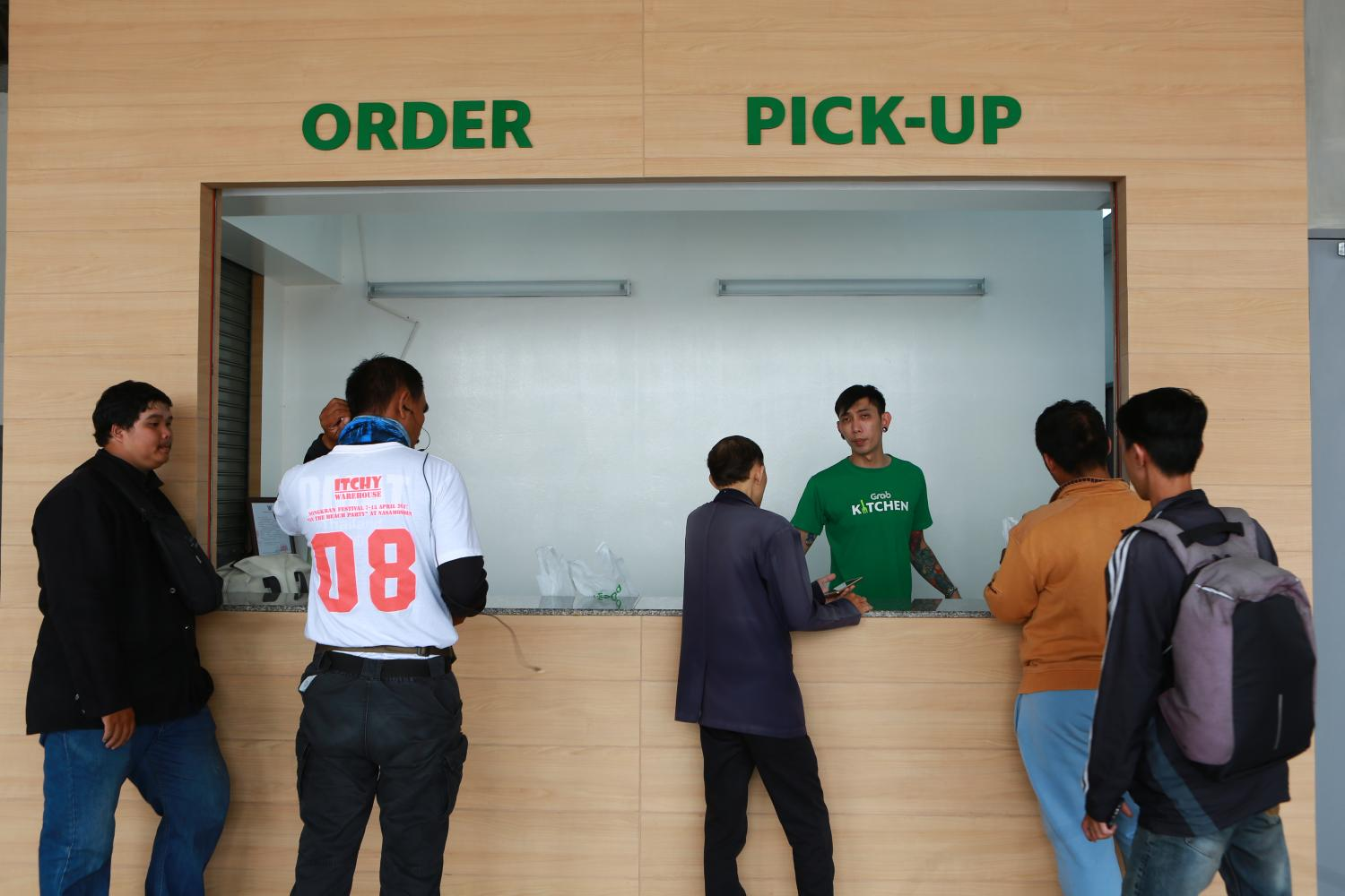 Delivery boys order and pick up meals at GrabKitchen. Somchai Poomlard