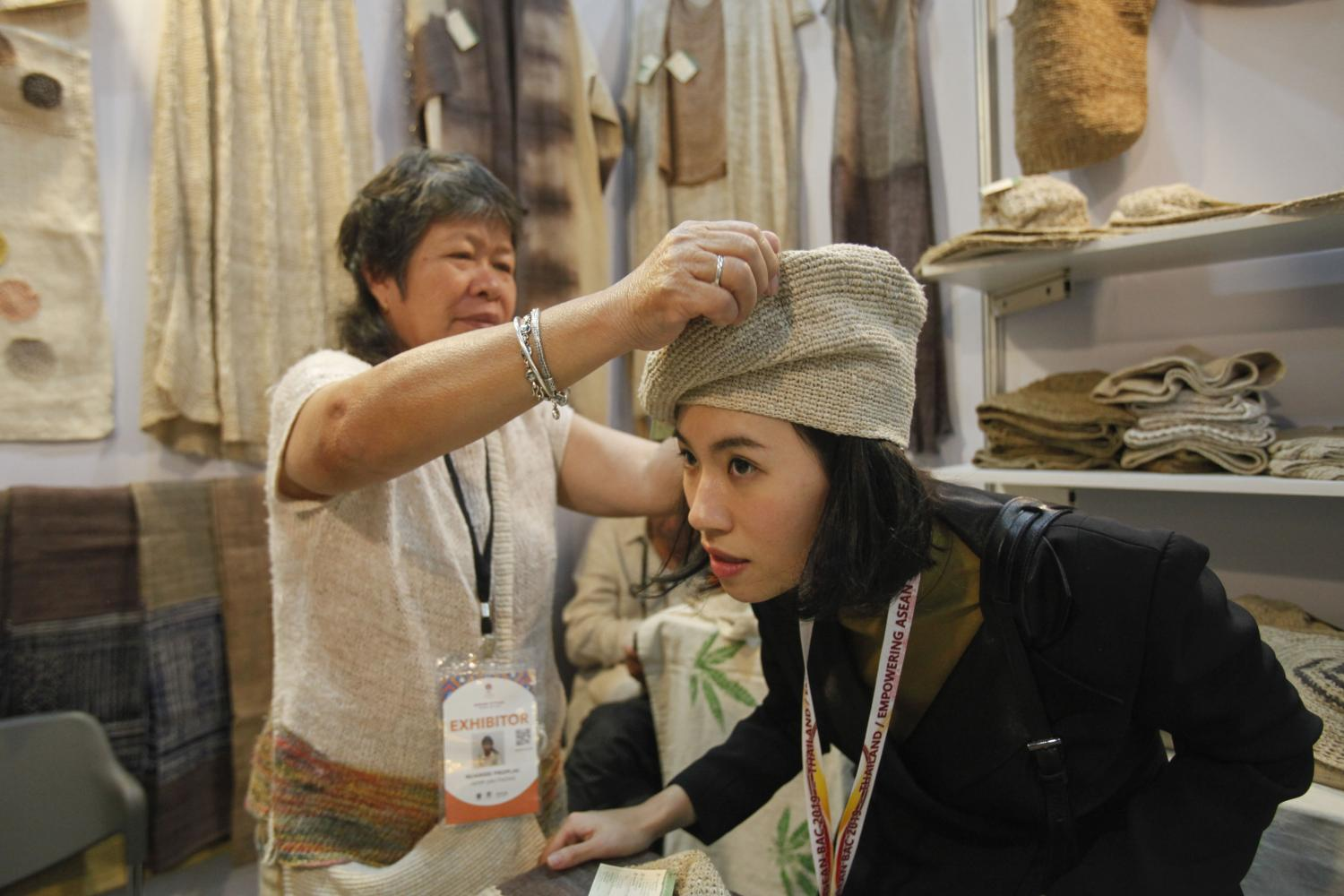 A vendor helps out a visitor at Asean Styles, a trade fair held on the sidelines of the 35th Asean Summit at Impact Exhibition and Convention Centre on Sunday.(Photo by Watcharawit Phudork)
