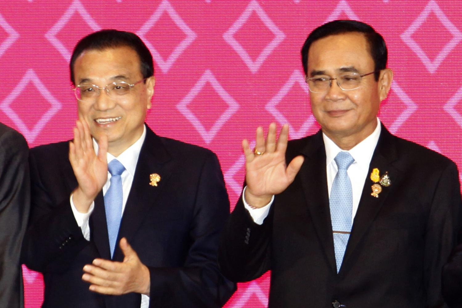 Chinese Premier Li Keqiang (left) and Prime Minister Prayut Chan-o-cha wave during a group photo session at the Asean-China Summit on Sunday. (Photo by Wichan Charoenkiatpakul)