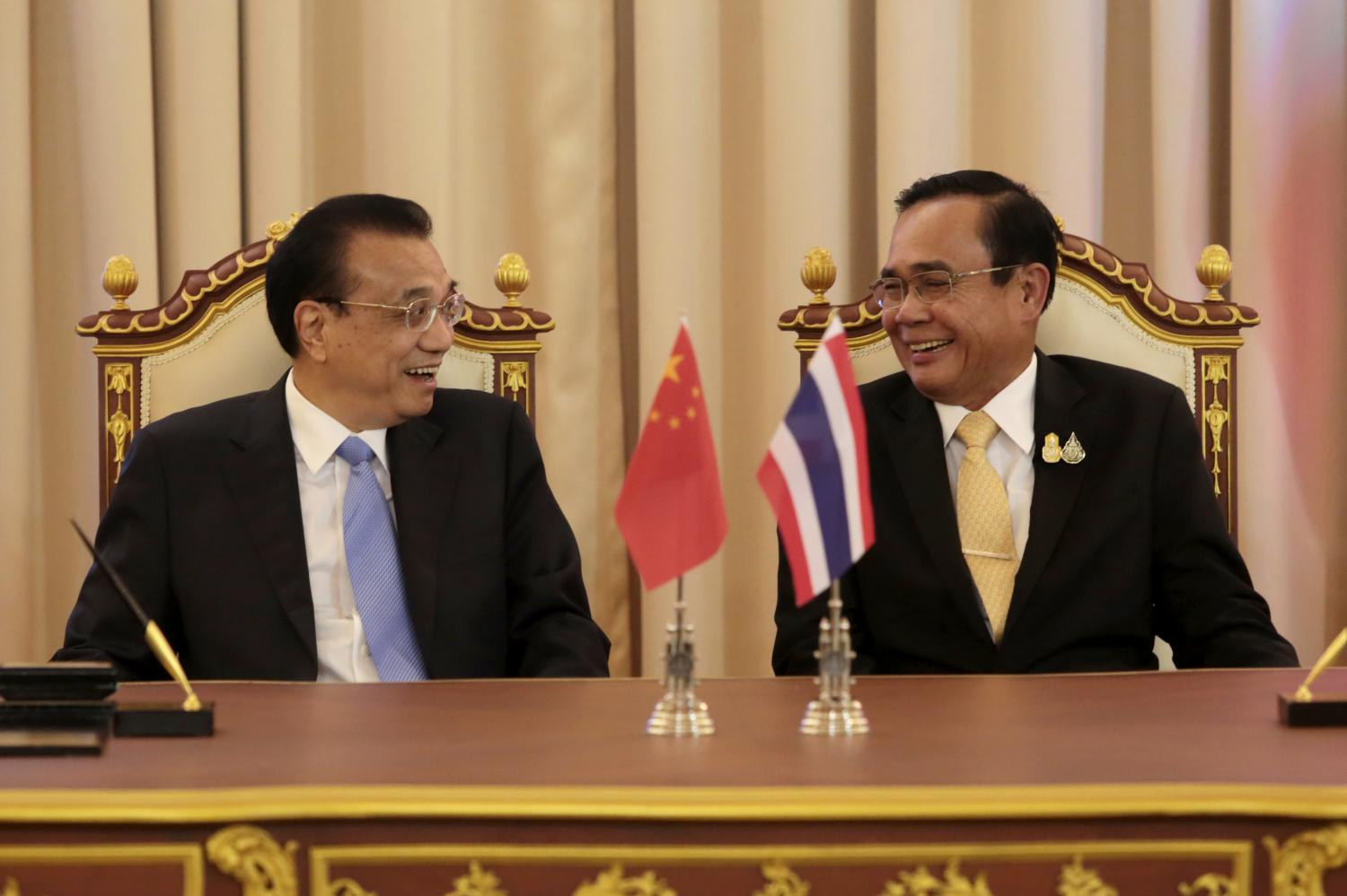 Prime Minister Prayut Chan-o-cha shares a light moment with Chinese Premier Li Keqiang as they witness the signing of three memorandums of understanding on cooperation at Government House on Tuesday.Chanat Katanyu