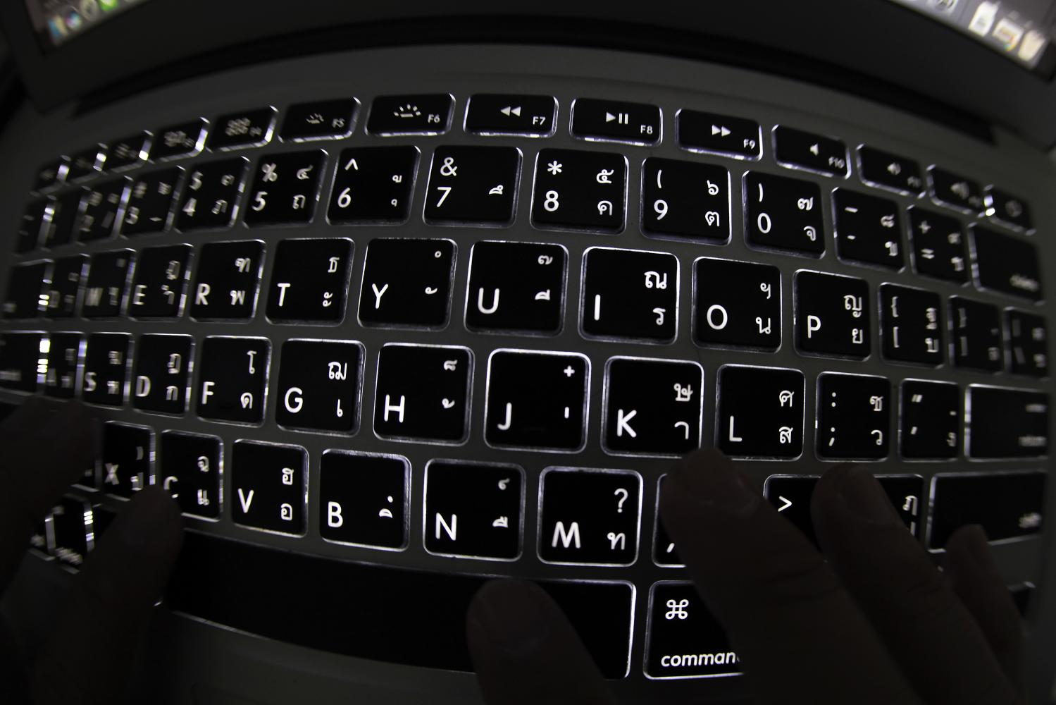 A man types on a computer keyboard as cybersecurity experts warn of an increase in cybercrimes arising from 5G. (Photo by Thanarak Khunton)