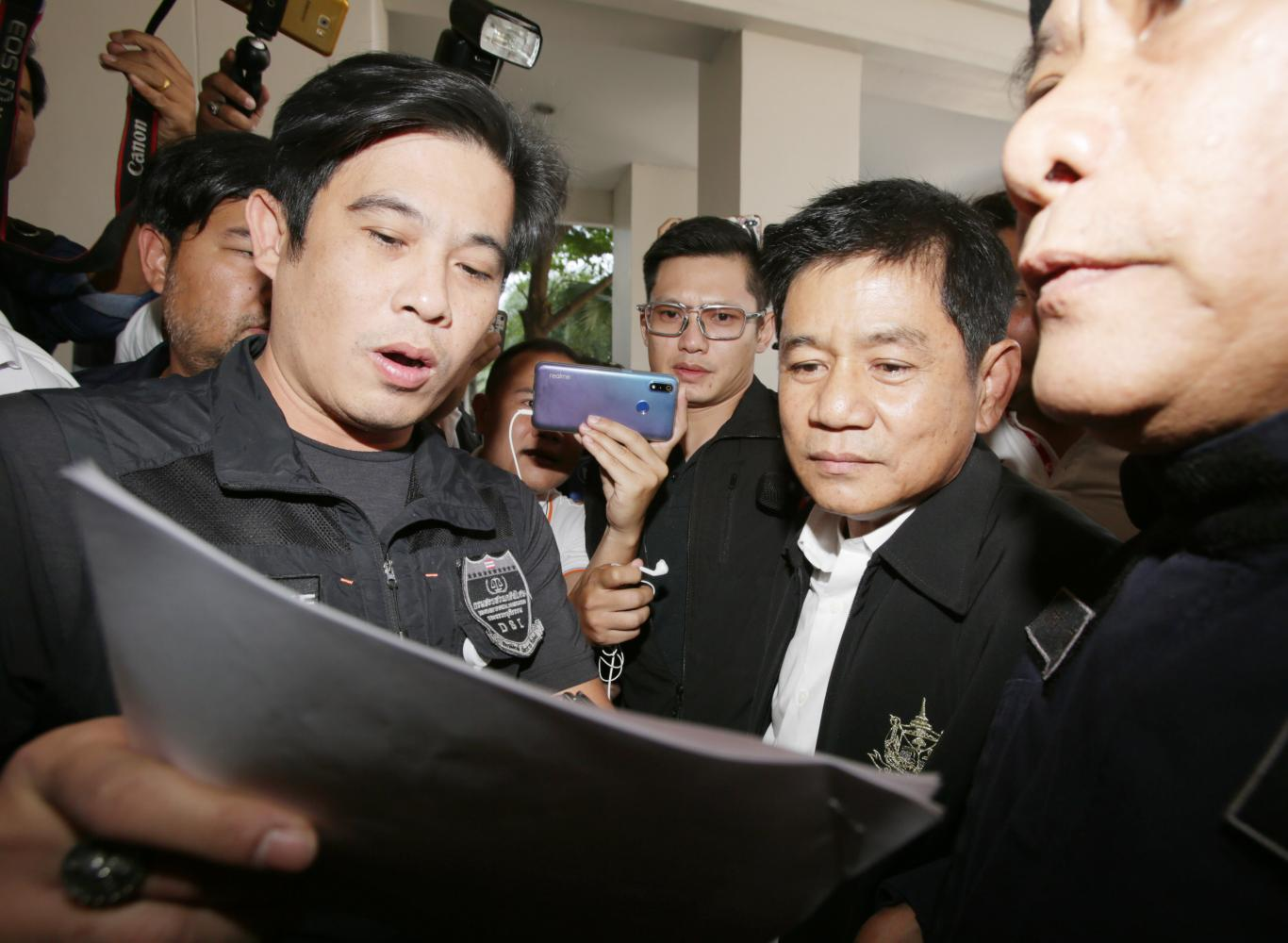 A Department of Special Investigation official yesterday reads the charges in the arrest warrant to Chaiwat Limlikit-aksorn, former chief of Kaeng Krachan National Park.PHOTOS by Apichit Jinakul