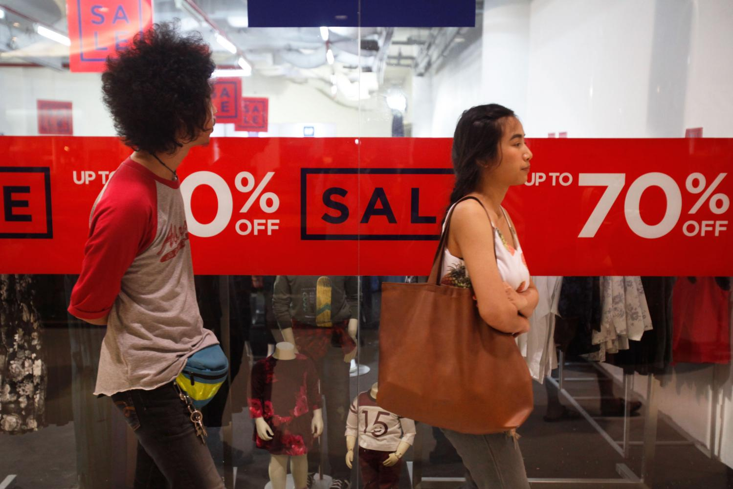 Shoppers walk past a sign advertising sales in a Bangkok shopping mall. Retailers are ramping up campaigns for the festive season.(Photo by Jiraporn Kuhakan)