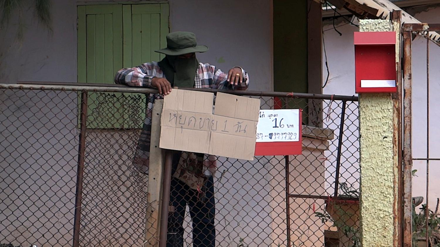 A worker puts up a sign at a poultry farm owned by Palang Pracharath Party MP Pareena Kraikupt in Ratchaburi's Chom Bung district on Wednesday, announcing its closure for one day.(Photo by Saichon Srinuanjan)