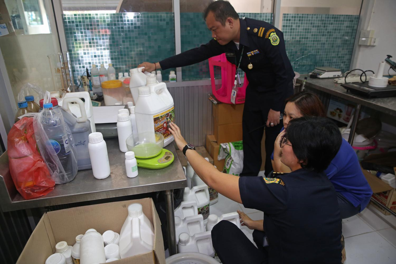 A Department of Special Investigation team inspects chemicals during a raid on premises linked with the sale of banned farm chemicals.Varuth Hirunyatheb