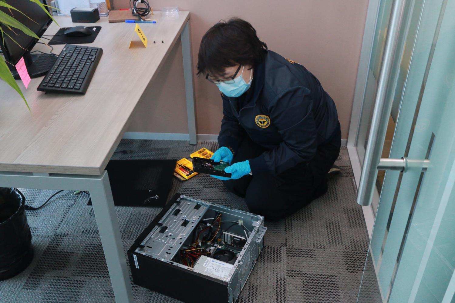 A DSI official inspects a computer to check for evidence that may link it with the Forex-3D scam in Bangkok on Friday.