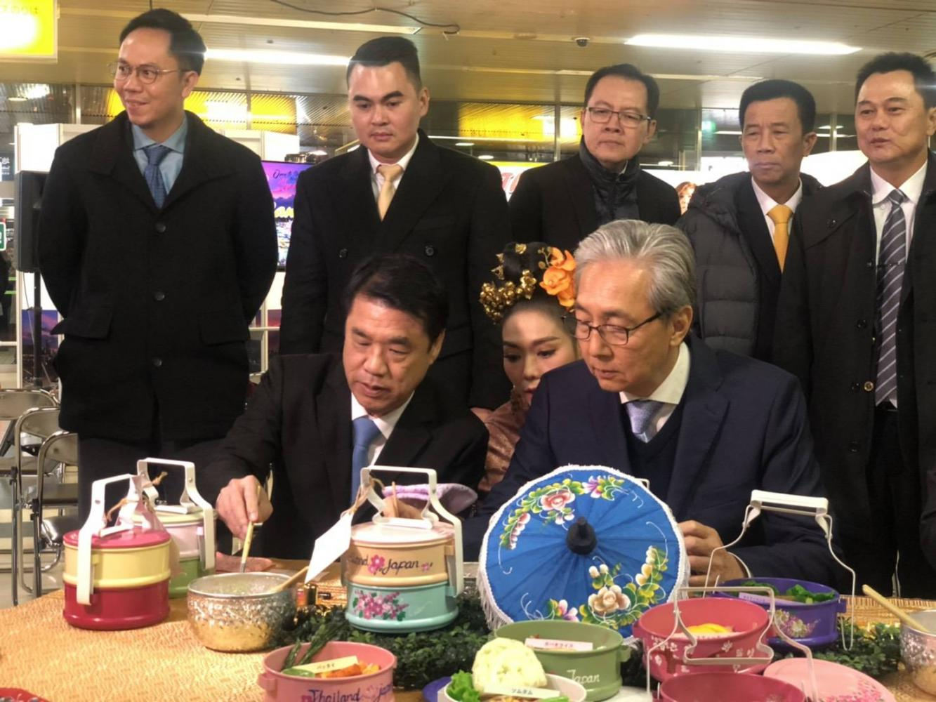 Mr Somkid, seated right front, and Industry Minister Suriya Jungrungreangkit, seated left front, paint Japanese bento to promote Thai tourism in Hokkaido on Nov 8.