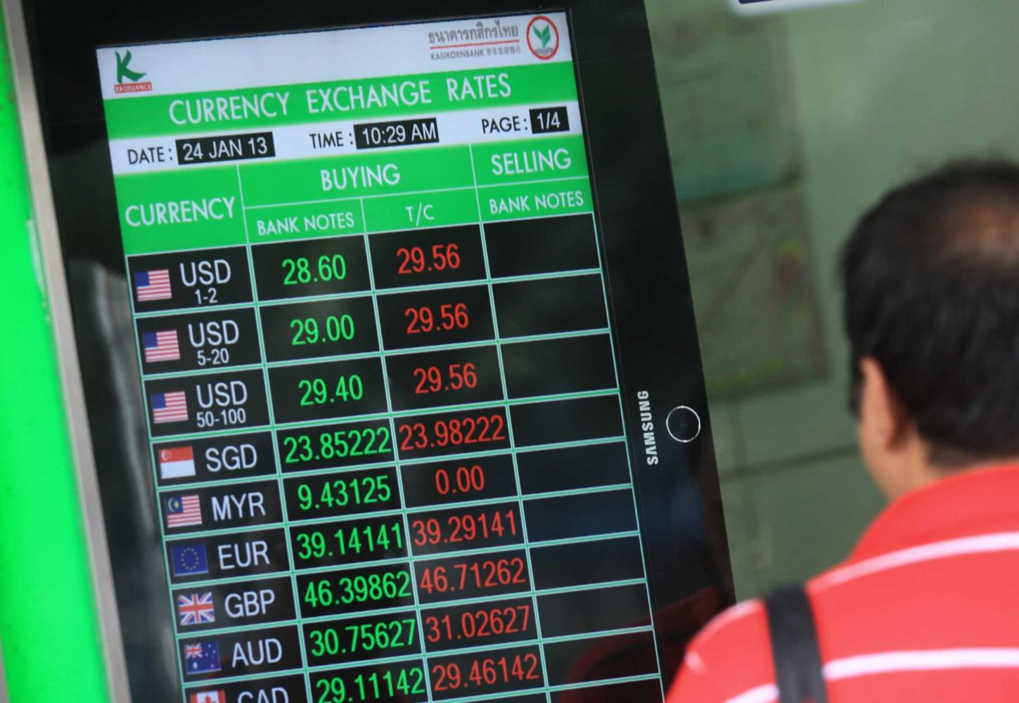 A man looks at a KBank foreign exchange board in Bangkok. The bank says the baht could strengthen to 29.25 to the US dollar by the end of 2020. Patipat Janthong