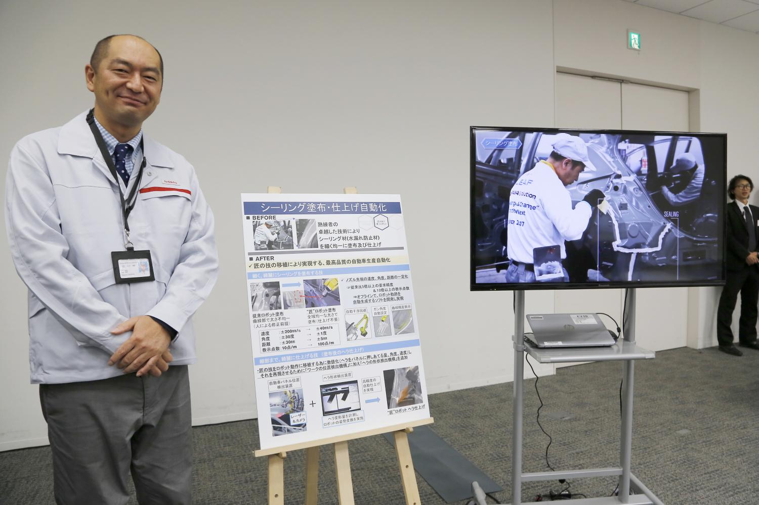 Engineer Makoto Yamada talks to reporters about using robotics for sealing as part of Nissan Motor Corp's new production methods during a press conference at the company's headquarter in Yokohama on Thursday. (AP photo)