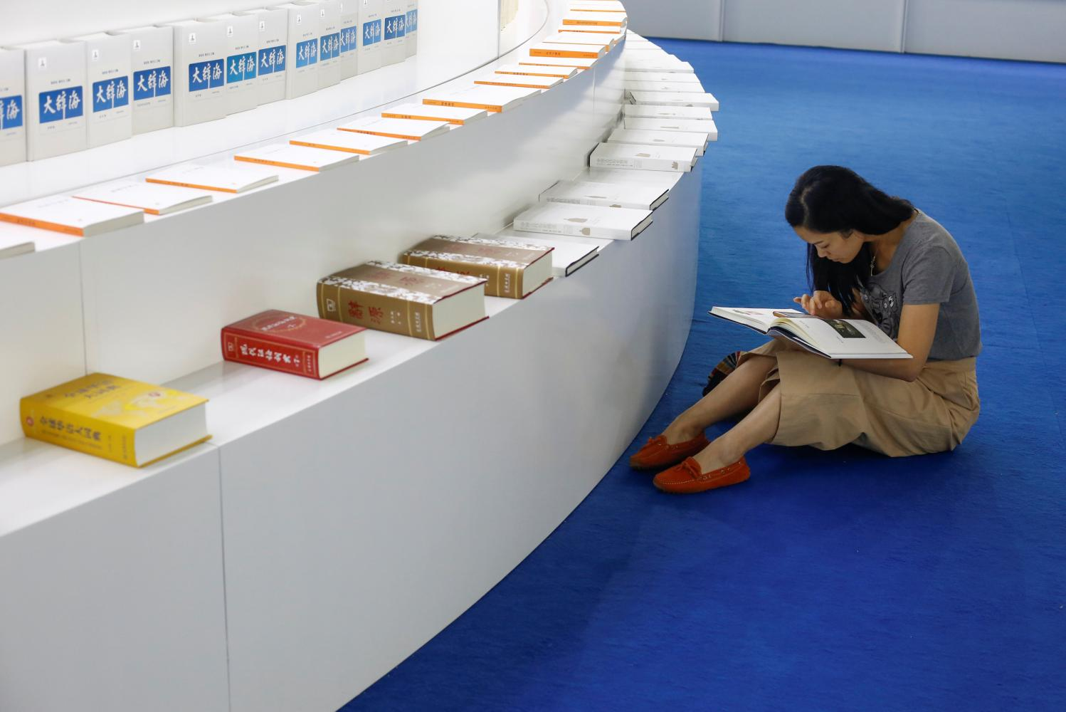 A visitor reads a book at the Beijing International Book Fair in 2017. Photo: Reuters File Photo