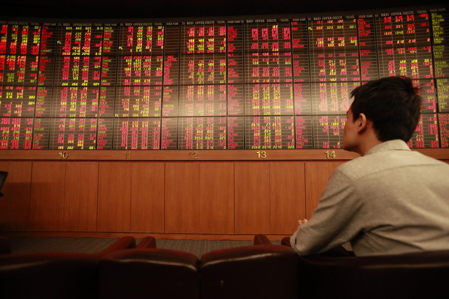 A man looks at share prices on an electronic board at Asia Plus Securities headquarters on Sathon Road.The SET index on Monday plunged the most among Asia Pacific bourses by 1.32%. (Bangkok Post file photo)