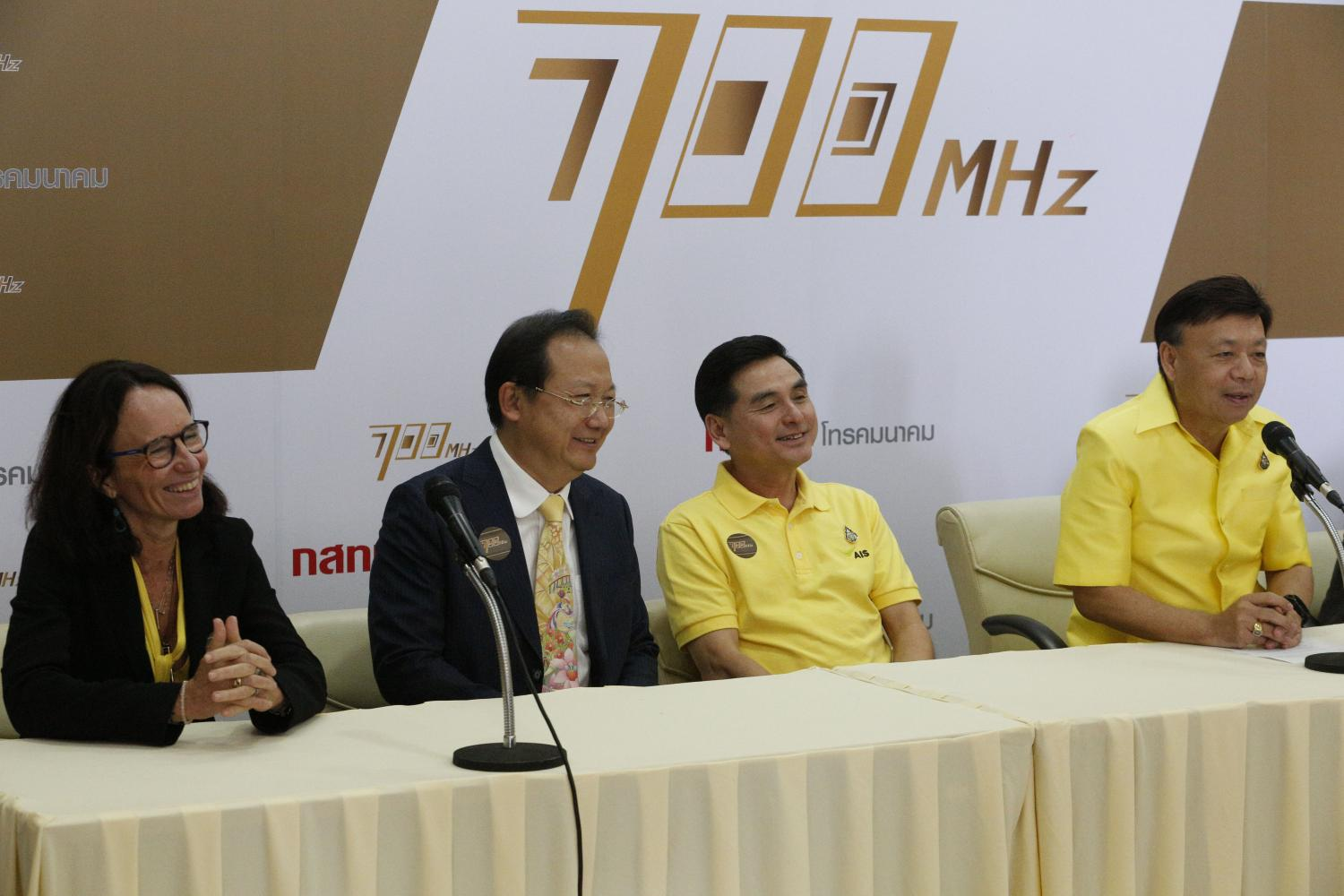 Mr Takorn (far right) with leaders of the three big operators at an auction held earlier this year. The companies have urged the NBTC to stipulate that the 2600MHz range must be used for 5G only.Pornprom Satrabhaya