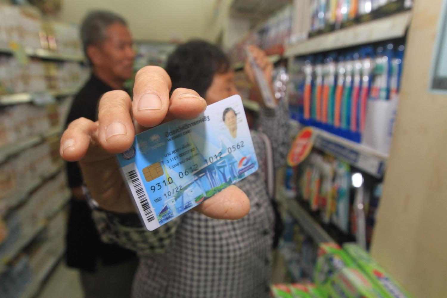 A woman shows a state welfare card while shopping for food and other necessities at a Thong Fah Pracharath shop. Somchai Poomlard