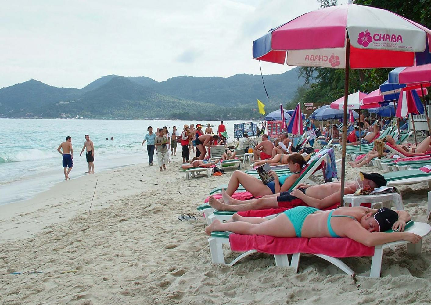 Foreign tourists lounge on Chaweng beach on Koh Samui. (Photo by Supapong Chaolan)