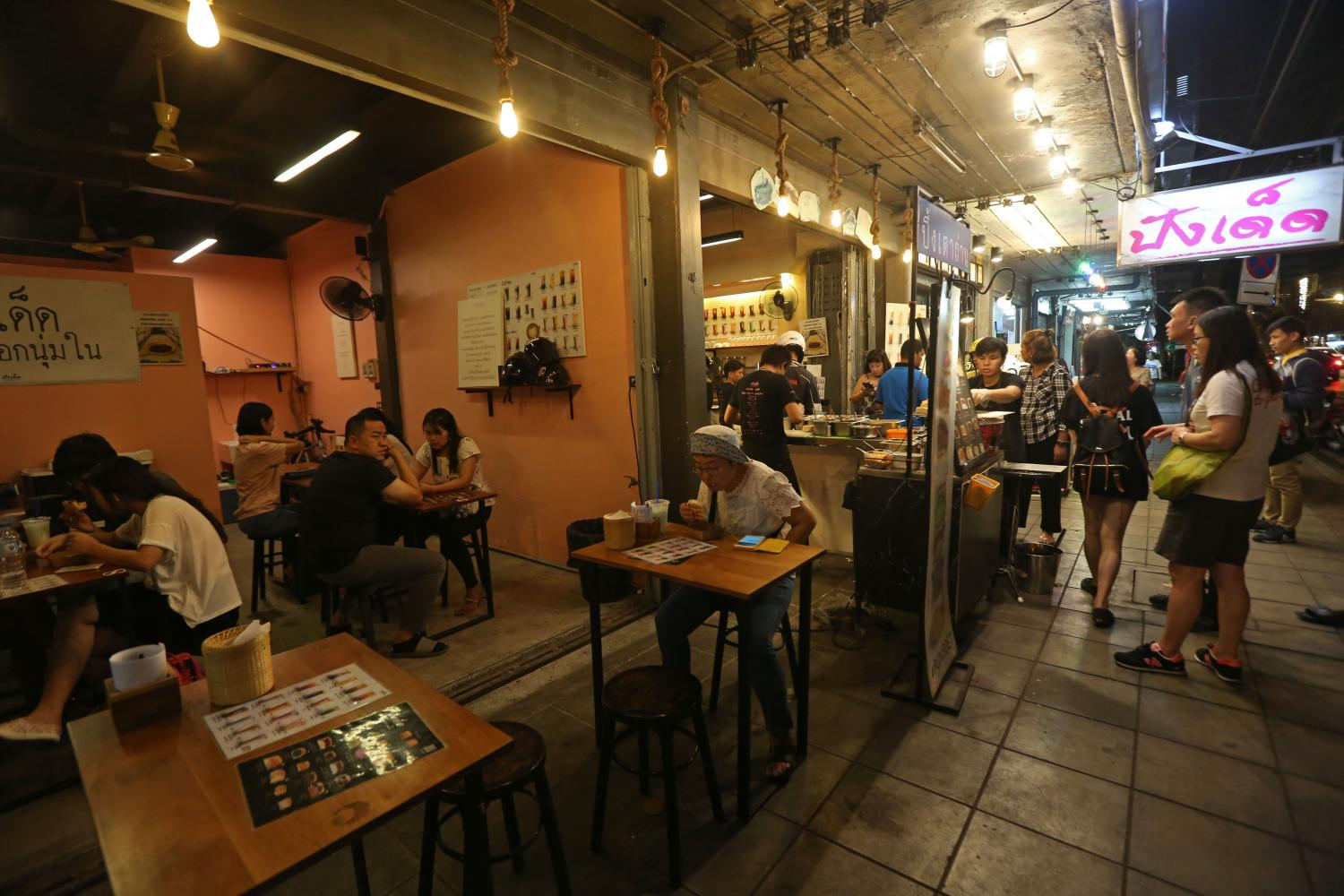 Customers sit at eateries on Bangkok's Bantadthong Road. Thailand is undergoing stagflation, with its economy suffering both a slowdown and high inflation at the same time, says economist Chartchai Parasuk.