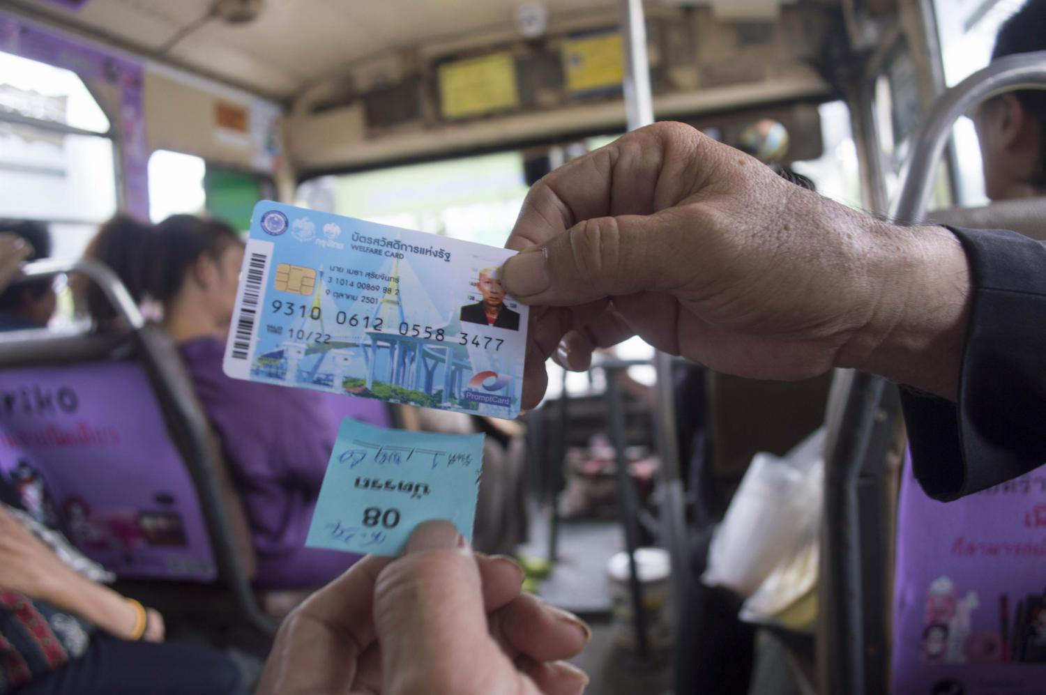 A welfare card holder shows a bus ticket given by a conductor who scanned the card for bus fare. The welfare card is available to Thai nationals aged 18 and up with an annual income of less than 100,000 baht.(Photo by Worrapon Phayakum)
