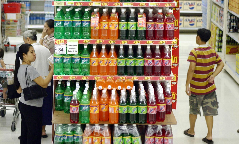 Consumers browse soft drinks at a Bangkok supermarket. Pattarachai Preechapanich