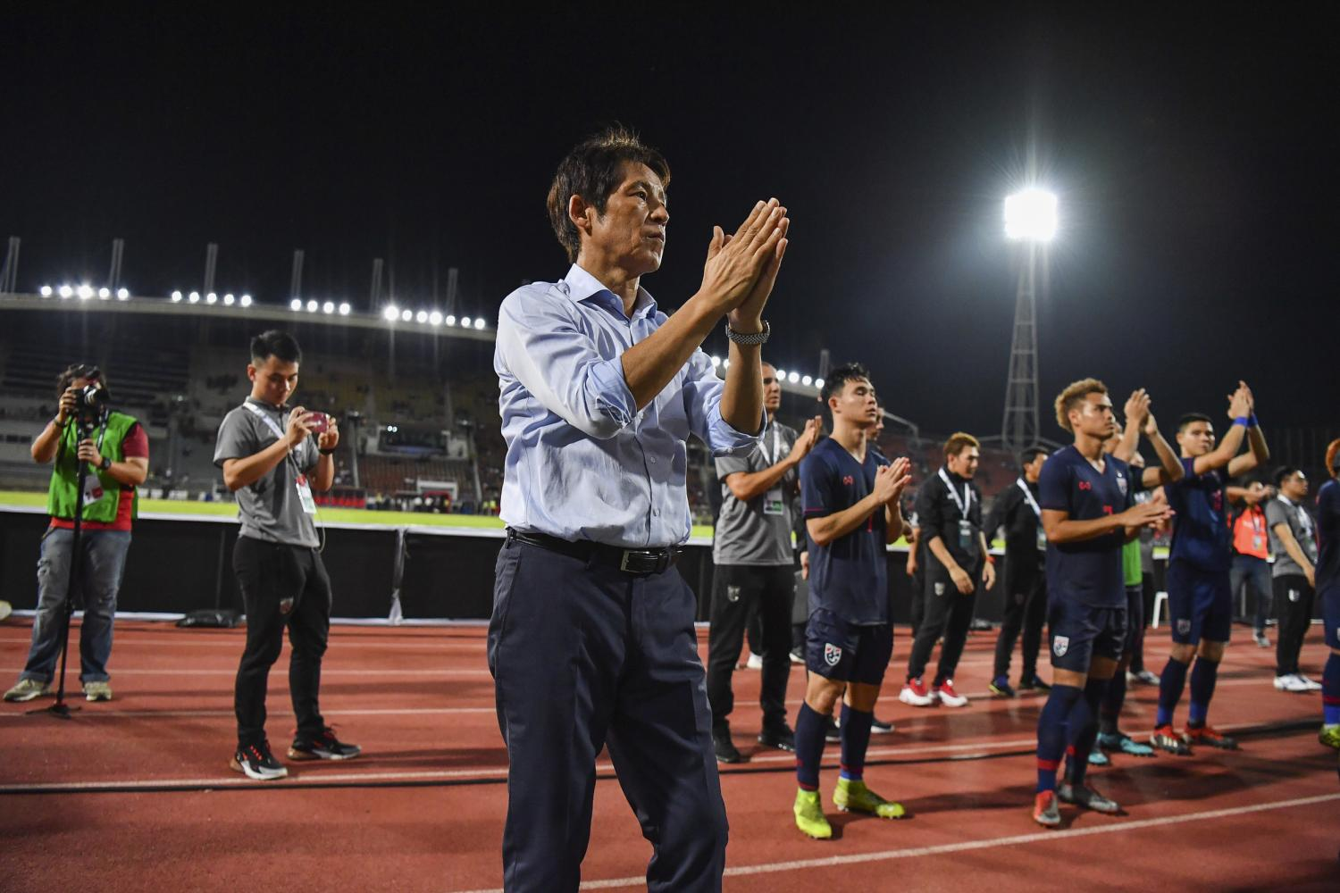 Thailand coach Akira Nishino and his players gesture to fans after a World Cup qualifier in Bangkok.