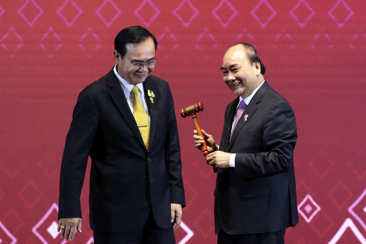 Prime Minister Prayut Chan-o-cha hands a gavel — the symbol of the Asean chairmanship — to Vietnam Prime Minister Nguyen Xuan Phuc.Patipat Janthong