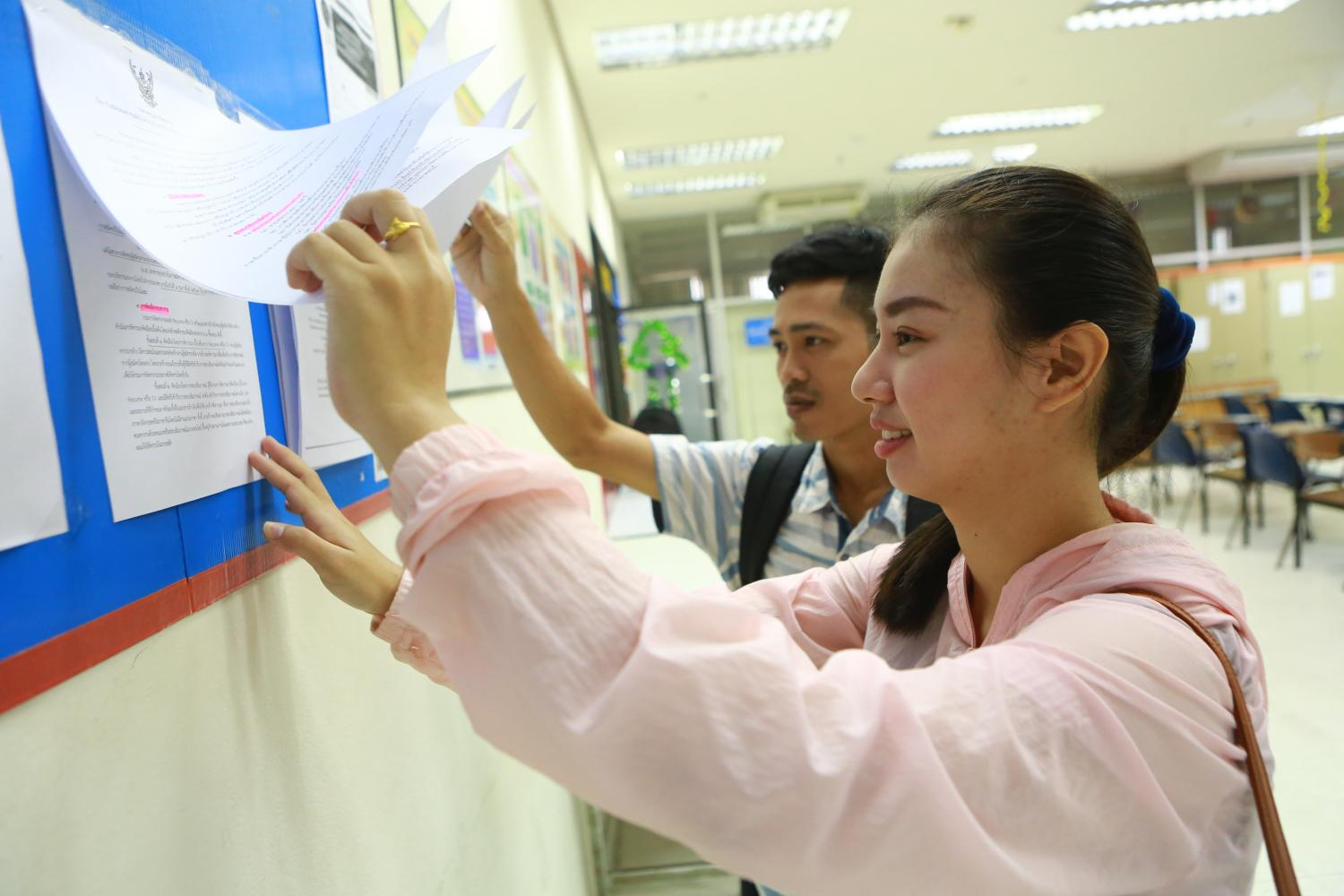 Job applicants read details of qualifications required by hotel and casino operators in Macao at the Labour Ministry which has offered them an opportunity to work abroad.(Photo by Somchai Poomlard)