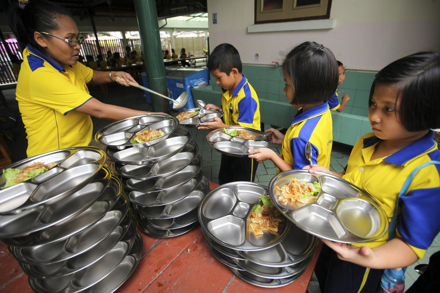 Students at Wat Makut Kasattriyaram School in Bangkok queue up for their midday meal. The school guarantees healthy food via its well-managed school lunch project.?(Photo by Patipat Janthong)