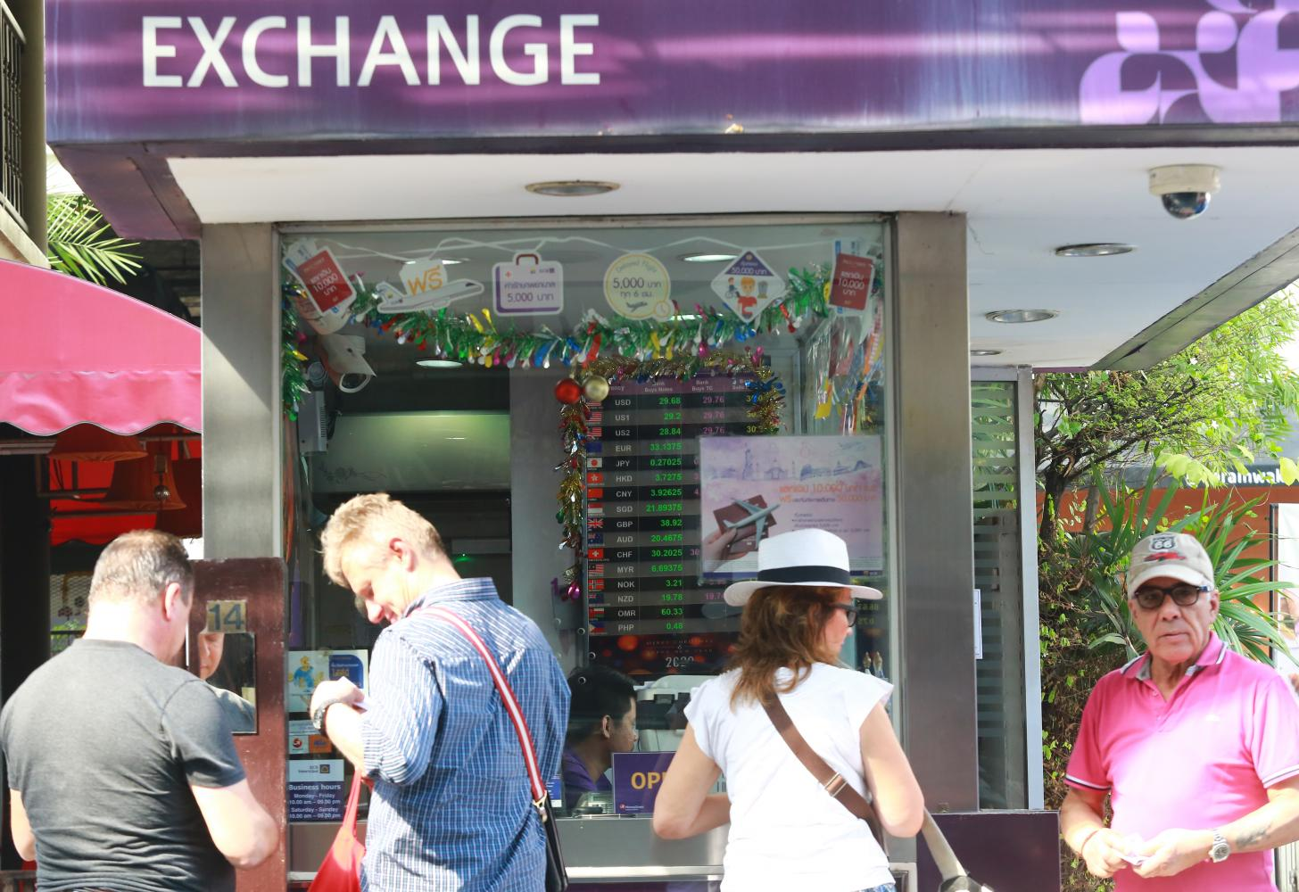 Tourists queue at a foreign exchange counter. The baht is down about 0.8% against the US dollar this year, trading at 30.15 on Friday.