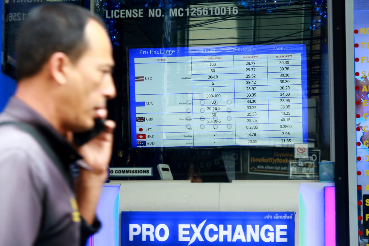 A man walks past a currency exchange booth in Bangkok. The Bank of Thailand has recently intervened in the foreign exchange market to try to weaken the baht. (Photo by Somchai Poomlard)