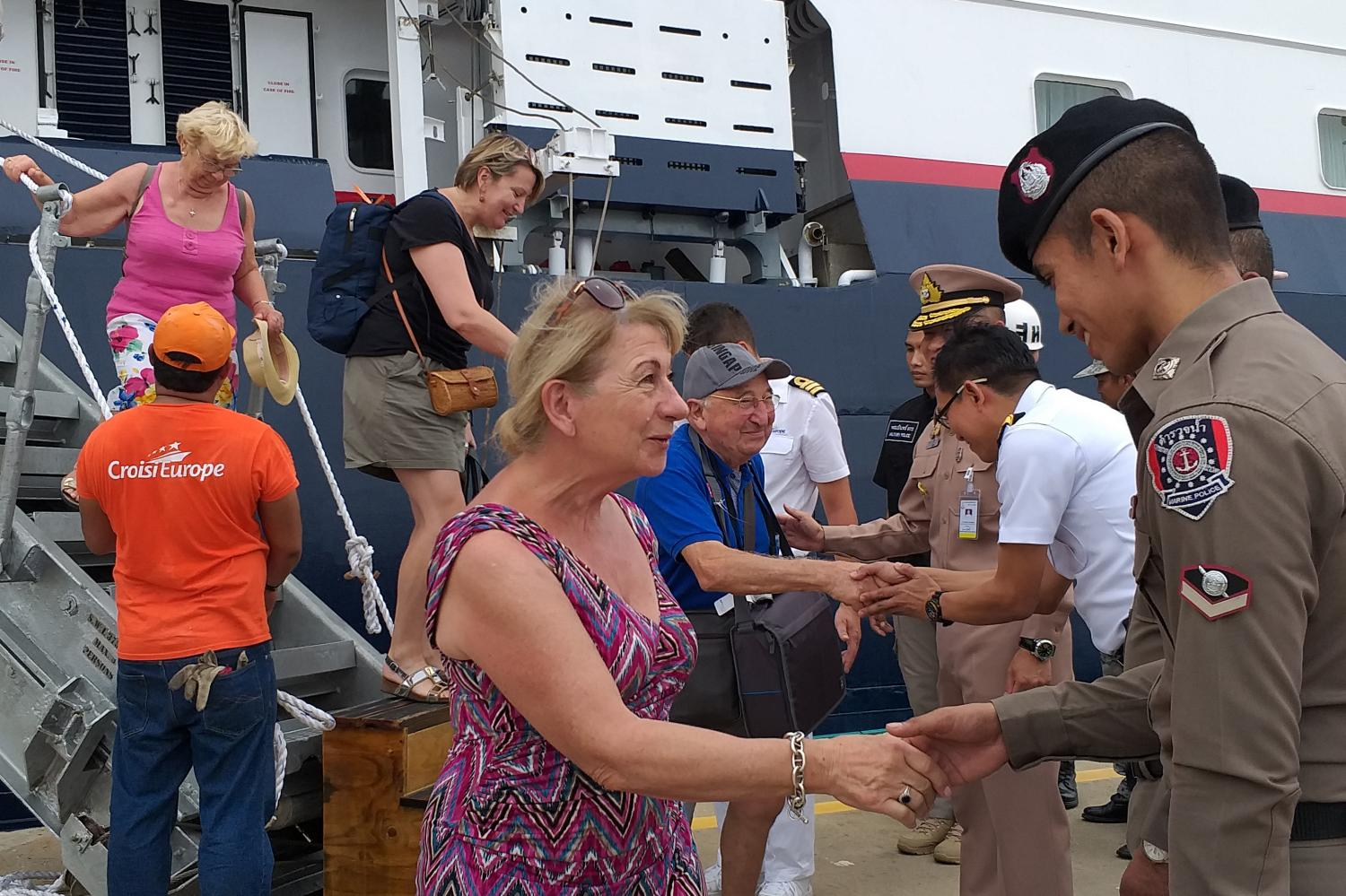 RESCUED: Tourists alight from Belgium-flagged cruiser 'La Belle Des Ocean' and thank officers after their ship hit the rocks near Pida islet. They were safely taken to a Phuket port.